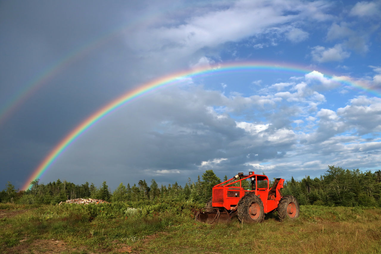 Tractor On Grassy Field Against Rainbow In Sky