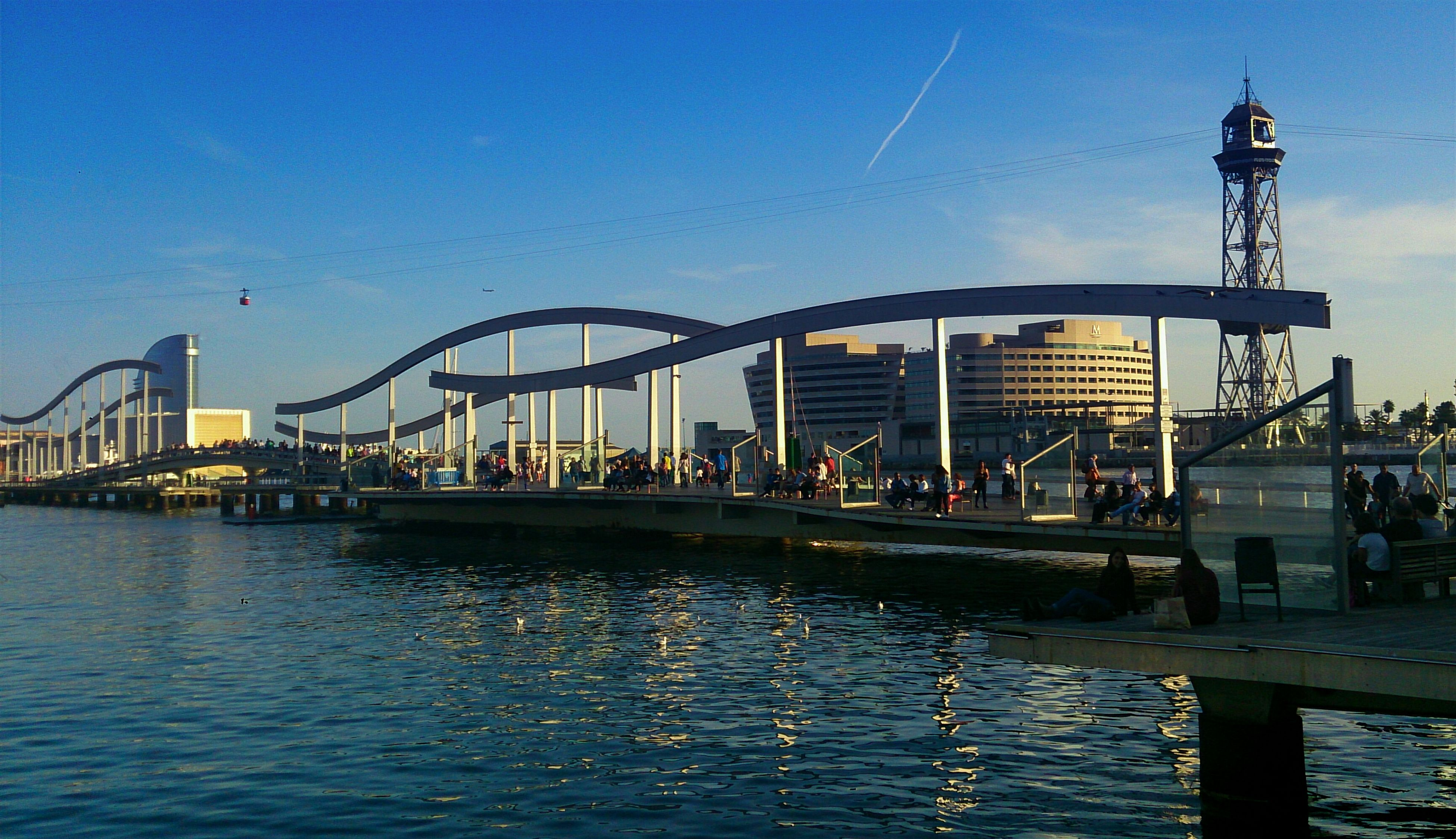 water, architecture, built structure, waterfront, blue, reflection, connection, building exterior, clear sky, bridge - man made structure, rippled, sky, river, sea, outdoors, bridge, pier, incidental people, no people, nature
