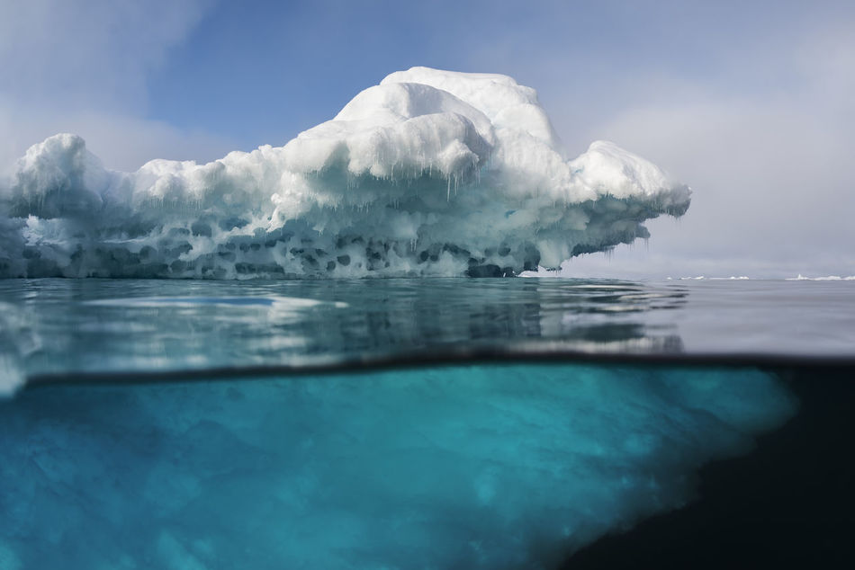 Split image above and underwater of an iceberg on the east coast of Greenland. Positioned in the Arctic, Greenland is especially vulnerable to climate change and has experienced record melting in recent years and is likely to contribute substantially to sea level rise as well as to possible changes in ocean circulation in the future. Glaciers worldwide store about 75 percent of the world's fresh water and if all land ice melted, sea level would rise approximately 70 meters worldwide. Underwater Greenland Greenpeace Arctic SaveTheArctic Iceberg Hello World Nature_collection Landscape Climatechange