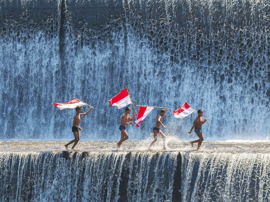 Boys having fun and waving indonesian flag by playing water in an artificial dam on the Tukad Unda dam, Bali, Indonesia ASIA Asian  Bali, Indonesia Children Fun Happy Indonesia Flag Jump Kids Leisure Activity Lifestyles Nature Outdoors People Portrait Run Summer Tourism Traditional Travel Travel Destinations Tukad Unda, Bali Water Waterfall Weather