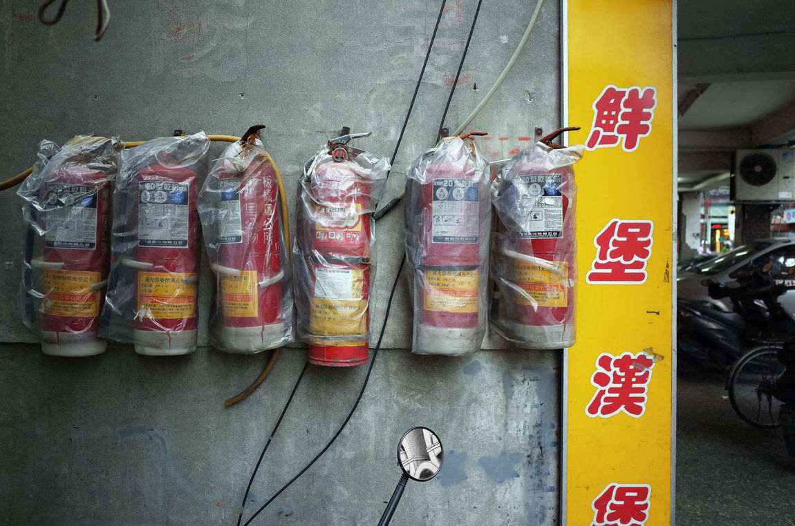 Fire Extinguisher Handing Out  Hanging On The Wall In A Row On The Streets Outdoors Plastic Bag Streetart Streetphotography Streetscape