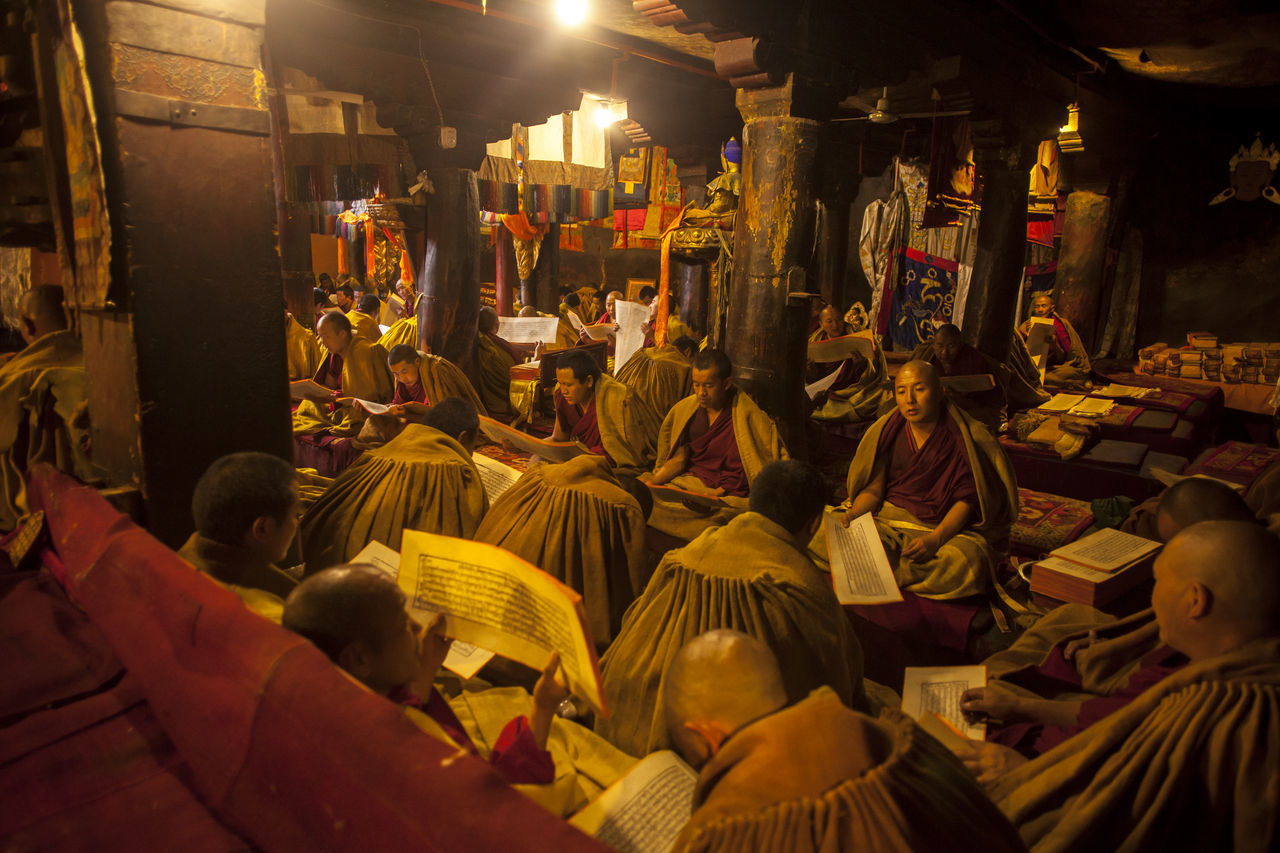Monk chanting and praying in the Monastery, Tibet. Adult Buddhism Chanting Cultures Devotion Indoors  Monastery Monk  Peace People Place Of Worship Red Religion Religion And Beliefs Script Spirituality Temple Tibet Tibetan  Yellow Editorial
