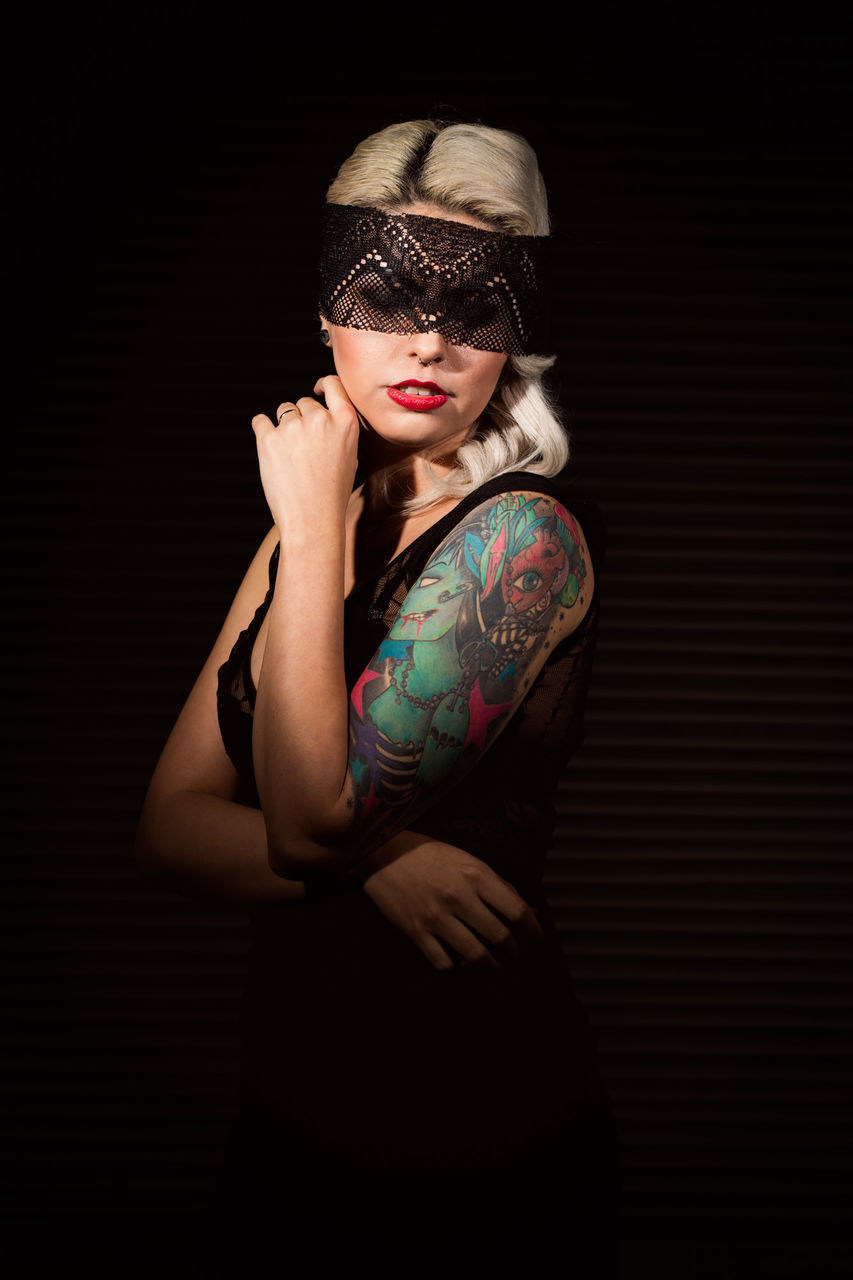 Woman With Tattoo Wearing Mask While Standing Against Black Background