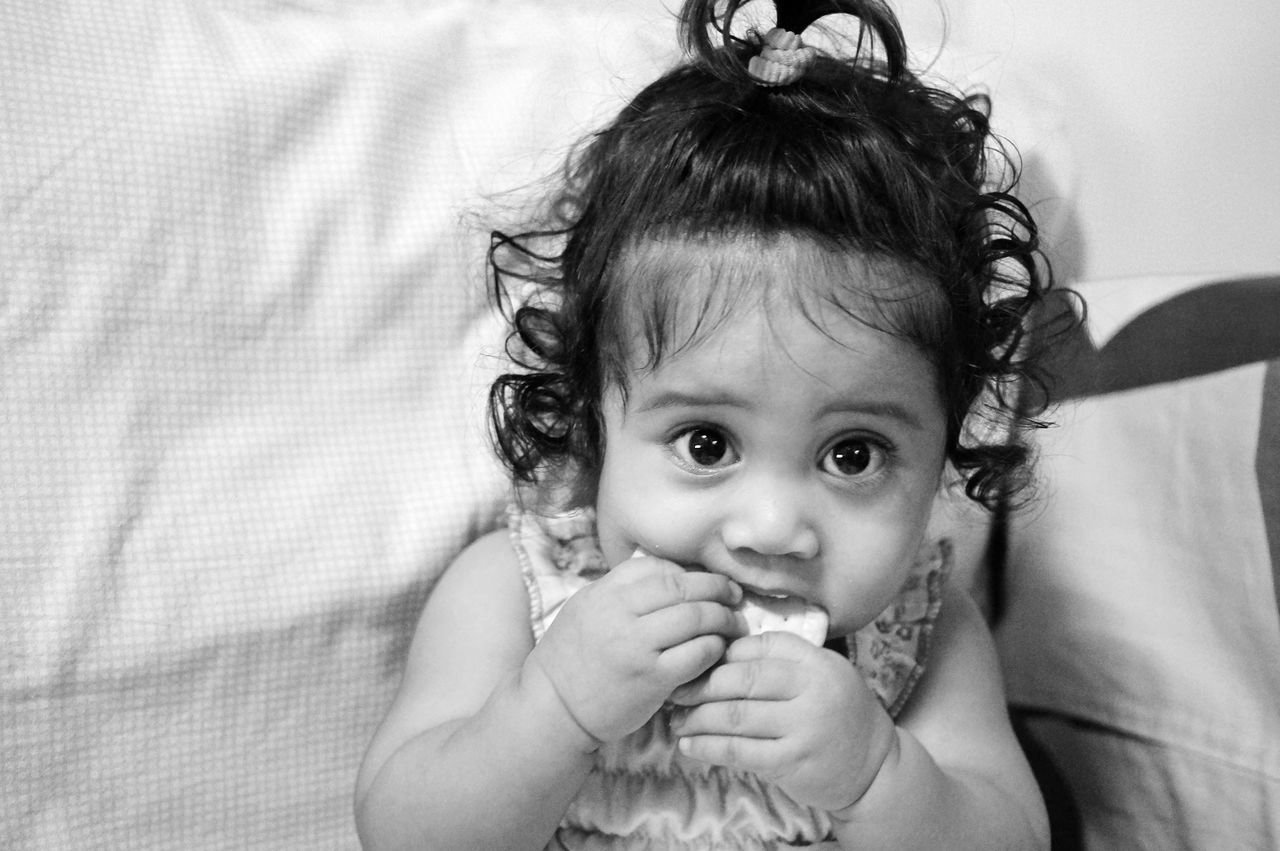Portrait Of Cute Baby Girl Eating Biscuit