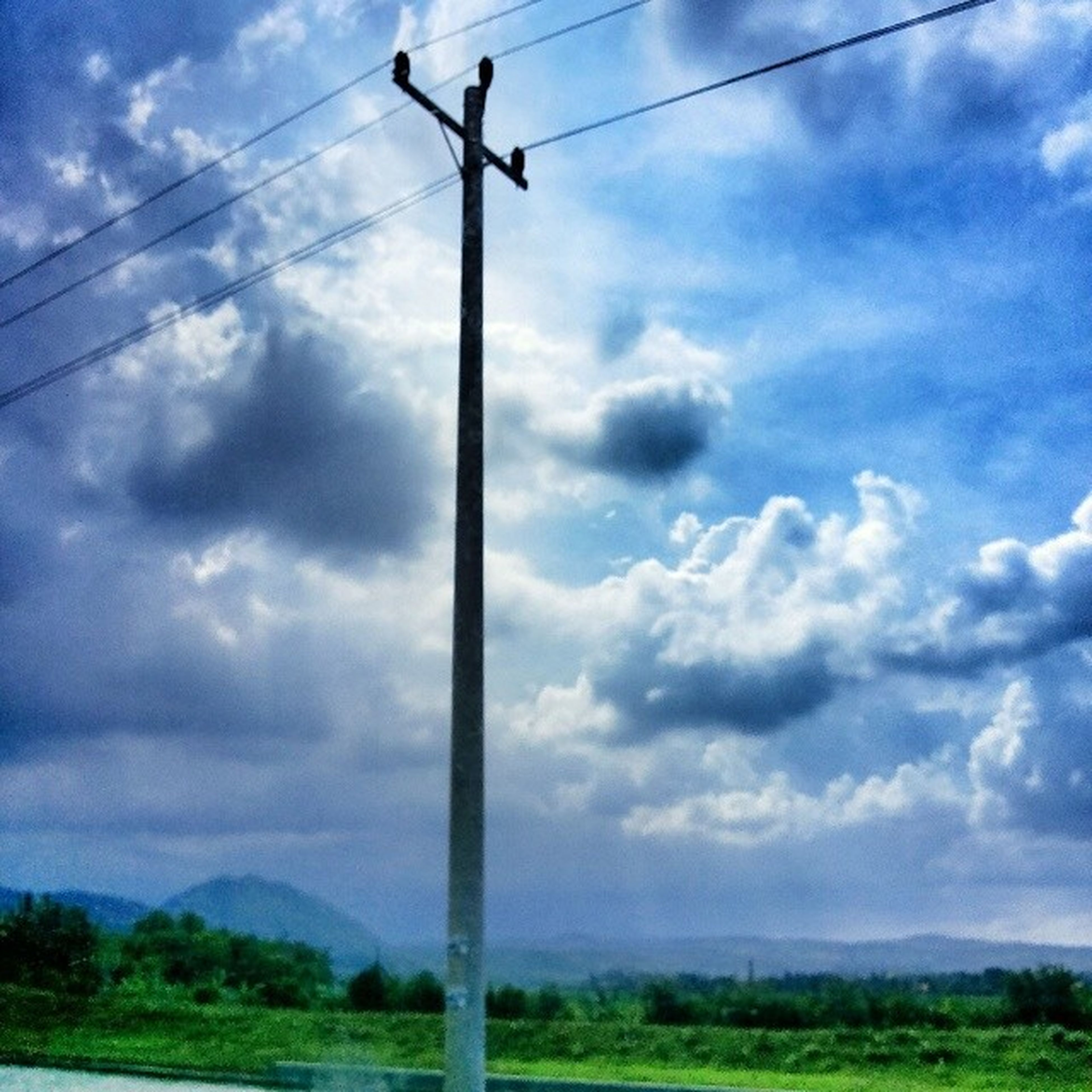 sky, power line, electricity pylon, electricity, cloud - sky, power supply, cable, fuel and power generation, cloudy, cloud, connection, landscape, tranquility, field, tranquil scene, technology, pole, nature, low angle view, scenics