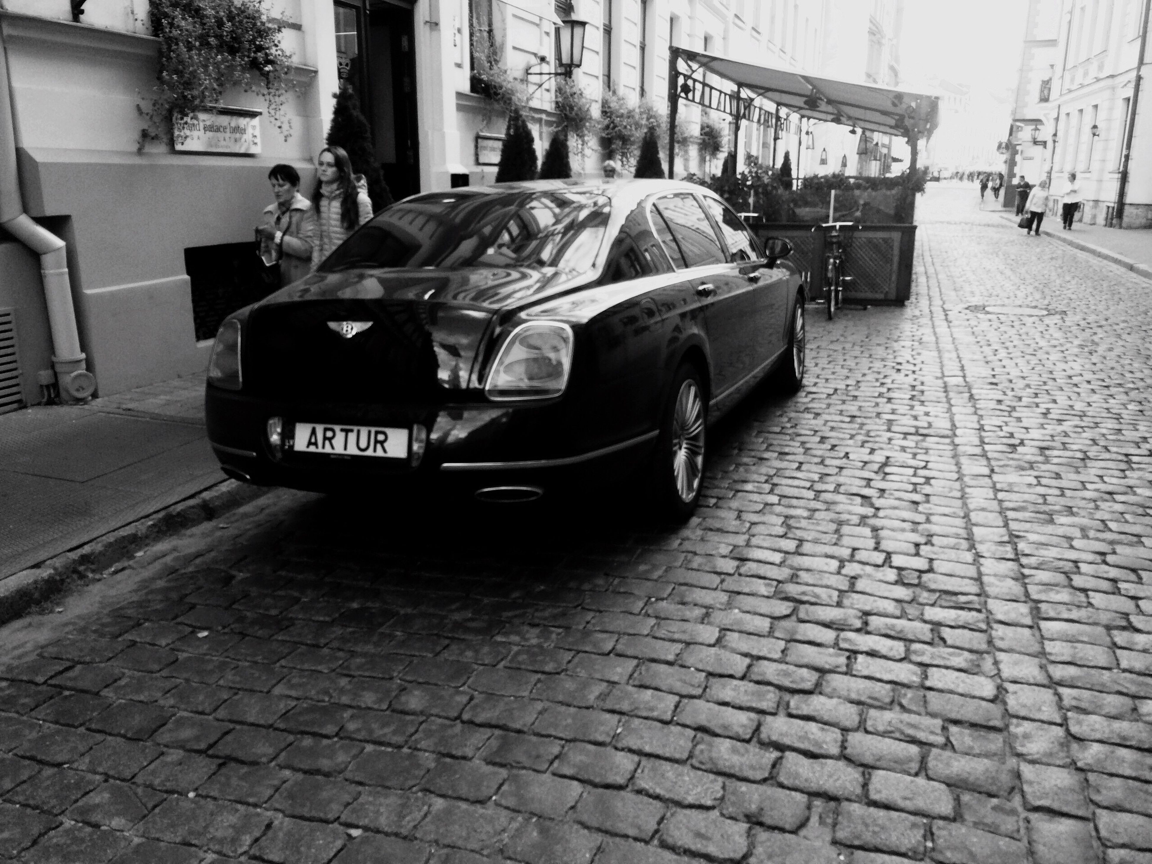 car, transportation, street, land vehicle, architecture, built structure, building exterior, cobblestone, city, mode of transport, road, stationary, day, city street, city life, outdoors, cobbled, paving stone, no people, the way forward
