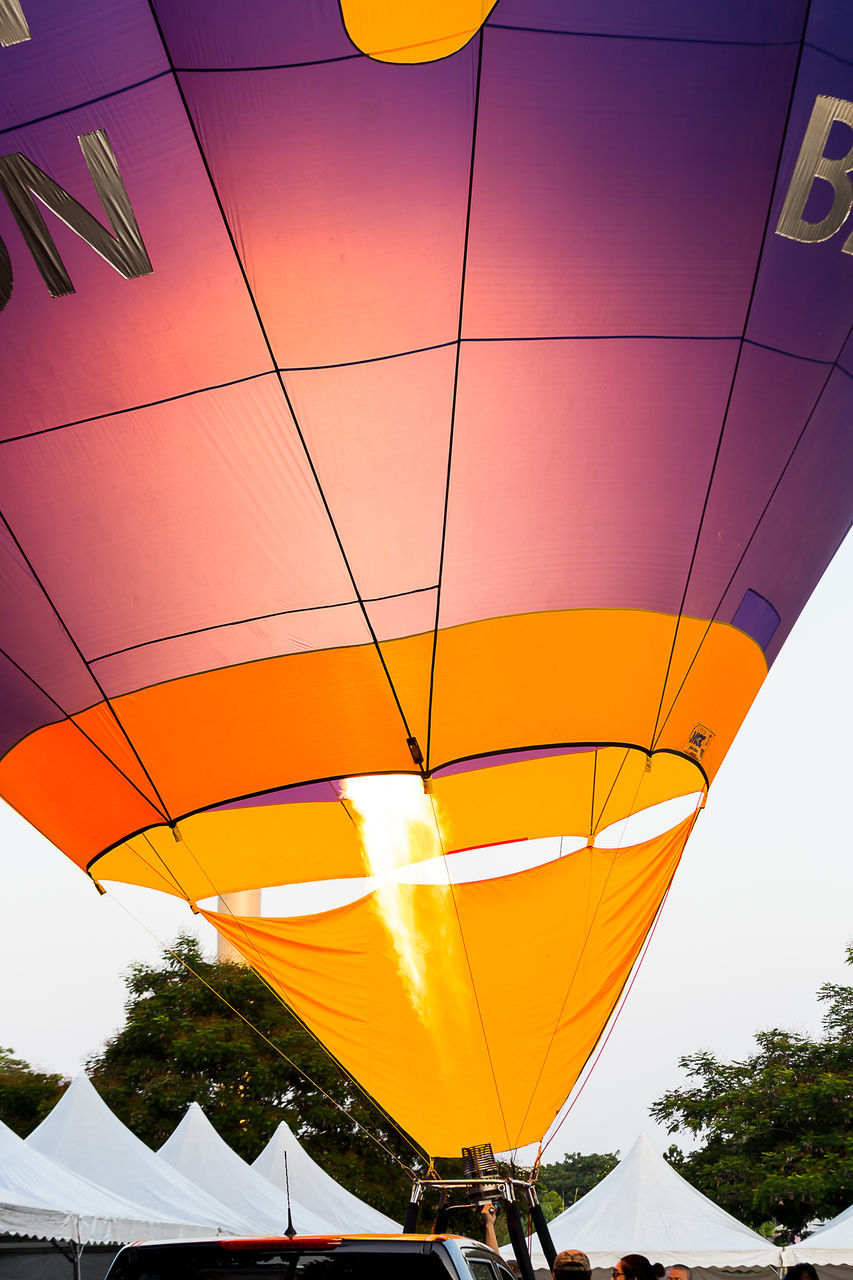 low angle view, hot air balloon, transportation, flying, multi colored, outdoors, sky, tree, no people, day, architecture