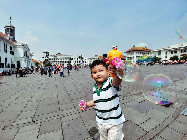 Childhood Sky Child Fun Day Multi Colored People Playing Large Group Of People Bubble Wand Full Length Crowd Building Exterior City Building Kid Architecture Historical Building Real People Outdoors Bubbles Bubble Gun Gun Toy Human Body Part Human Hand