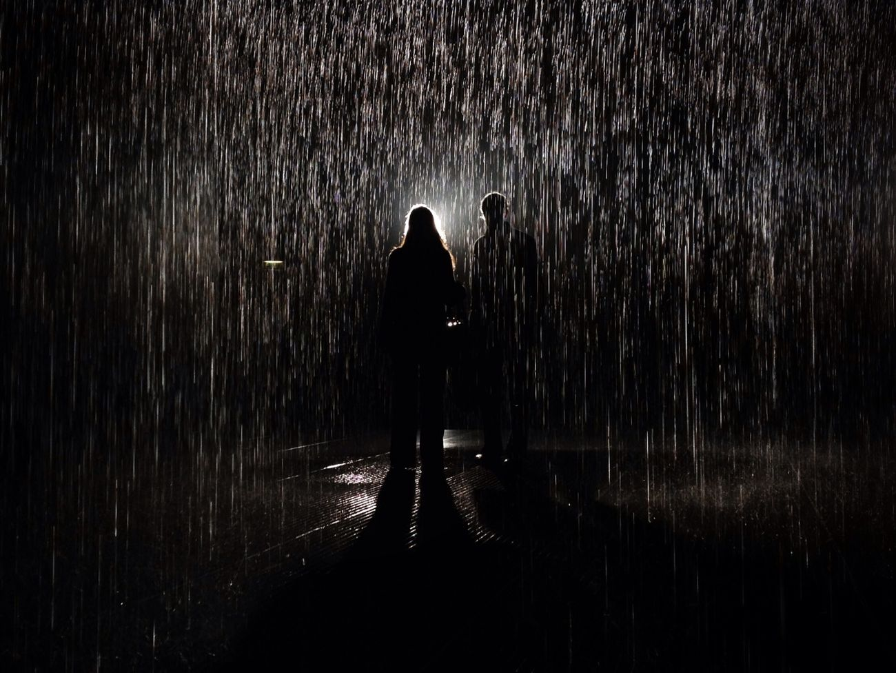 A couple walk through Random International's Rain Room at the Barbican Centre in London