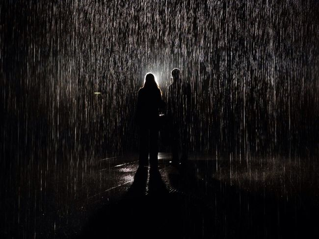 A couple walk through Random International's Rain Room at the Barbican Centre in London