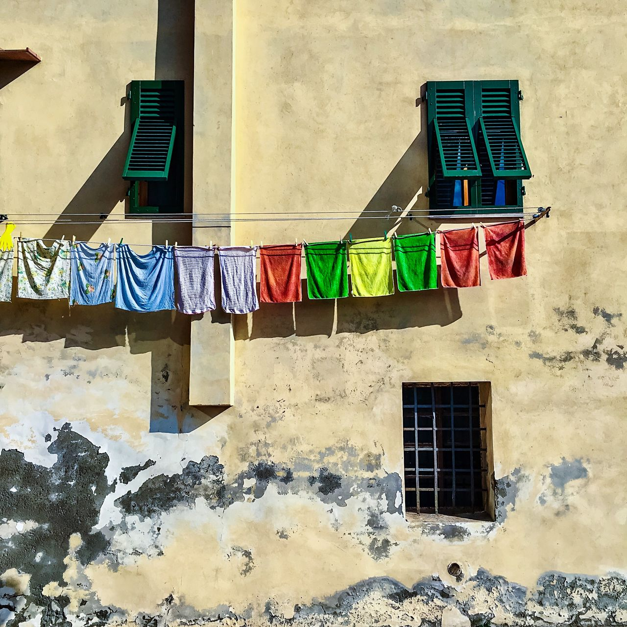 building exterior, architecture, built structure, building, window, flag, residential building, multi colored, clothesline, no people, day, laundry, outdoors, drying, hanging, low angle view