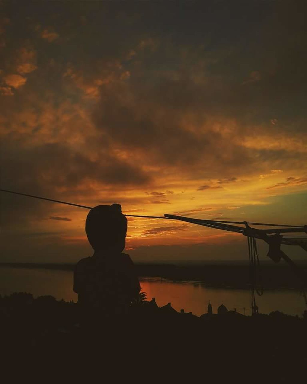 sunset, silhouette, orange color, sky, one person, real people, childhood, water, cloud - sky, nature, beauty in nature, sea, scenics, leisure activity, outdoors, boys, lifestyles, fishing tackle, standing, child, tree, children only, people