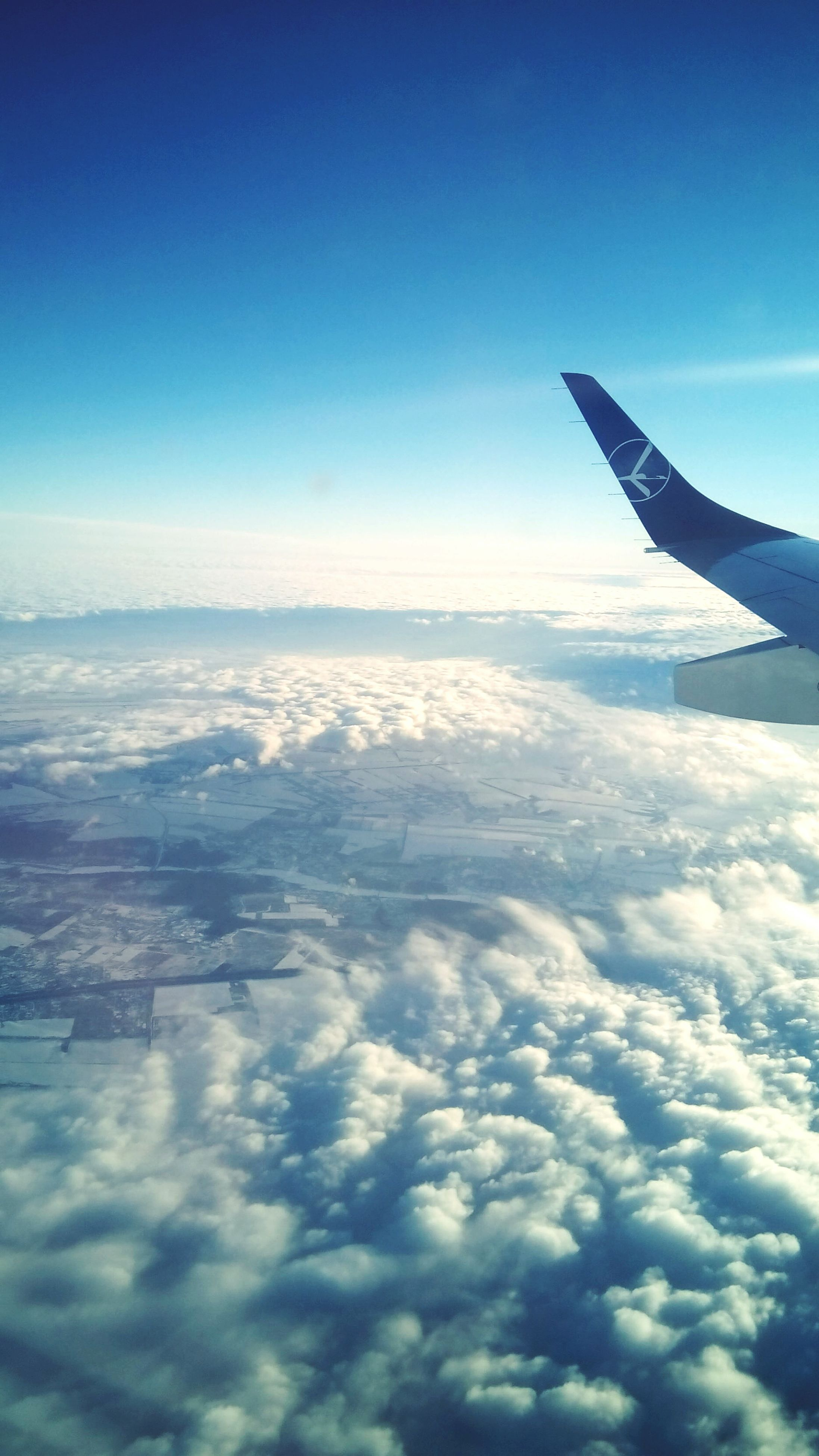 airplane, flying, aircraft wing, air vehicle, blue, aerial view, sky, beauty in nature, scenics, snow, landscape, part of, nature, tranquil scene, travel, tranquility, mid-air, winter, cropped, transportation