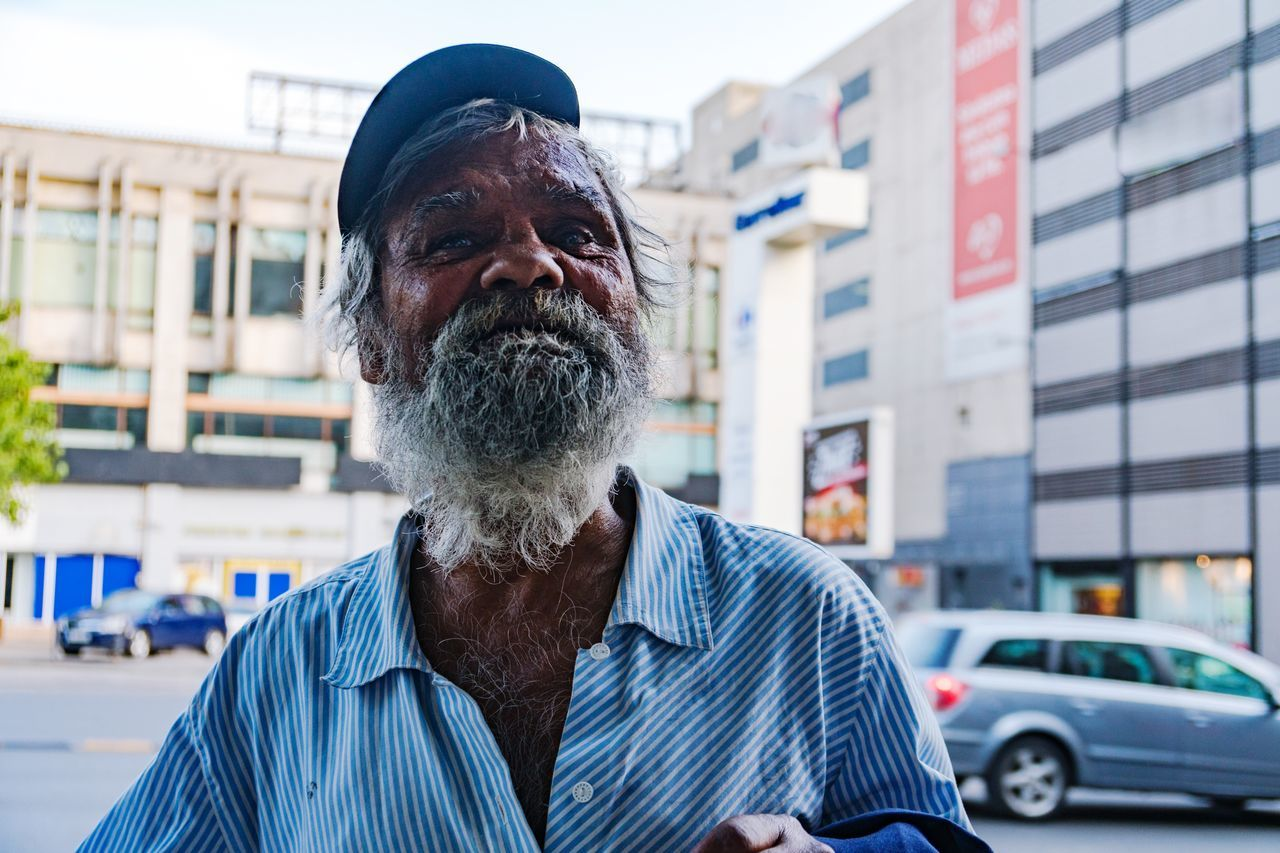 real people, senior adult, one person, senior men, beard, focus on foreground, outdoors, building exterior, mature men, lifestyles, architecture, front view, men, day, built structure, mature adult, headshot, portrait, close-up, city, sky, people