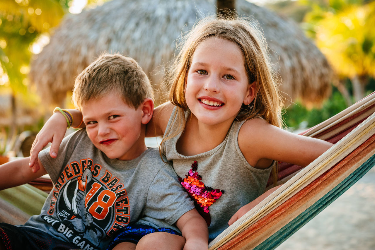 childhood, looking at camera, two people, portrait, leisure activity, outdoors, togetherness, girls, smiling, casual clothing, real people, sitting, day, boys, happiness, sibling, fun, bonding, blond hair, child, friendship, close-up, people
