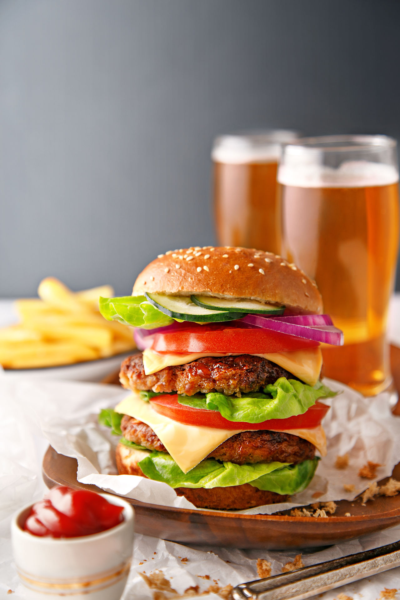 Tasty hamburger with french fries and beer in the background Bread Bun Cheese CheeseBurger Food And Drink Garnish Gourmet Ground Beef Hamburger Homemade Indoors  Lettuce Meal Meat Minced No People Prepared Potato Ready-to-eat Sesame Snack Studio Shot Take Out Food Tomato Unhealthy Eating Vegetable