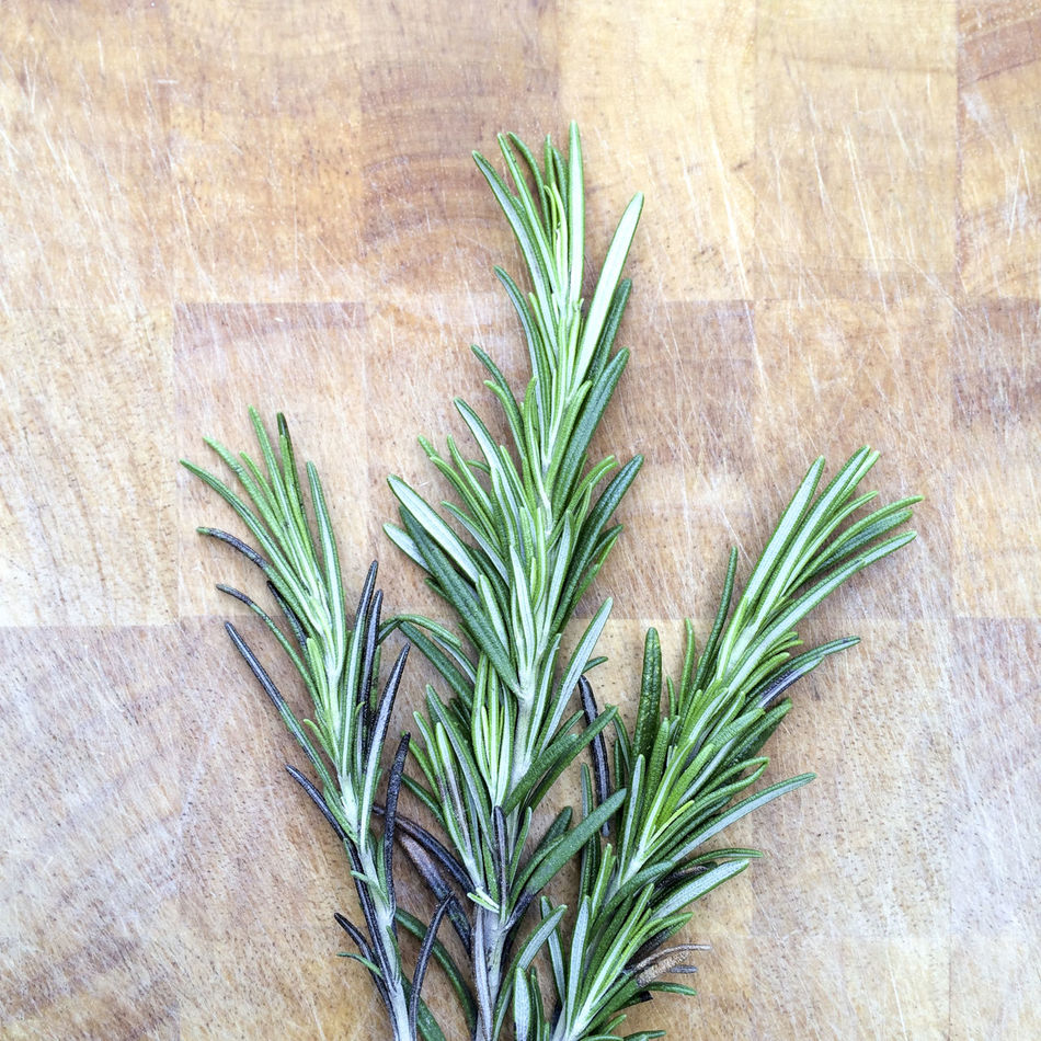 Sprigs of Rosemary on wooden chopping board Background Chopping Board Close Up Close-up Detail Flavouring Green Green Color Growth Herb Herbs High Angle View Ingredient Leaf Plant Rosemary Sprig Sprigs Surface Wood Wooden