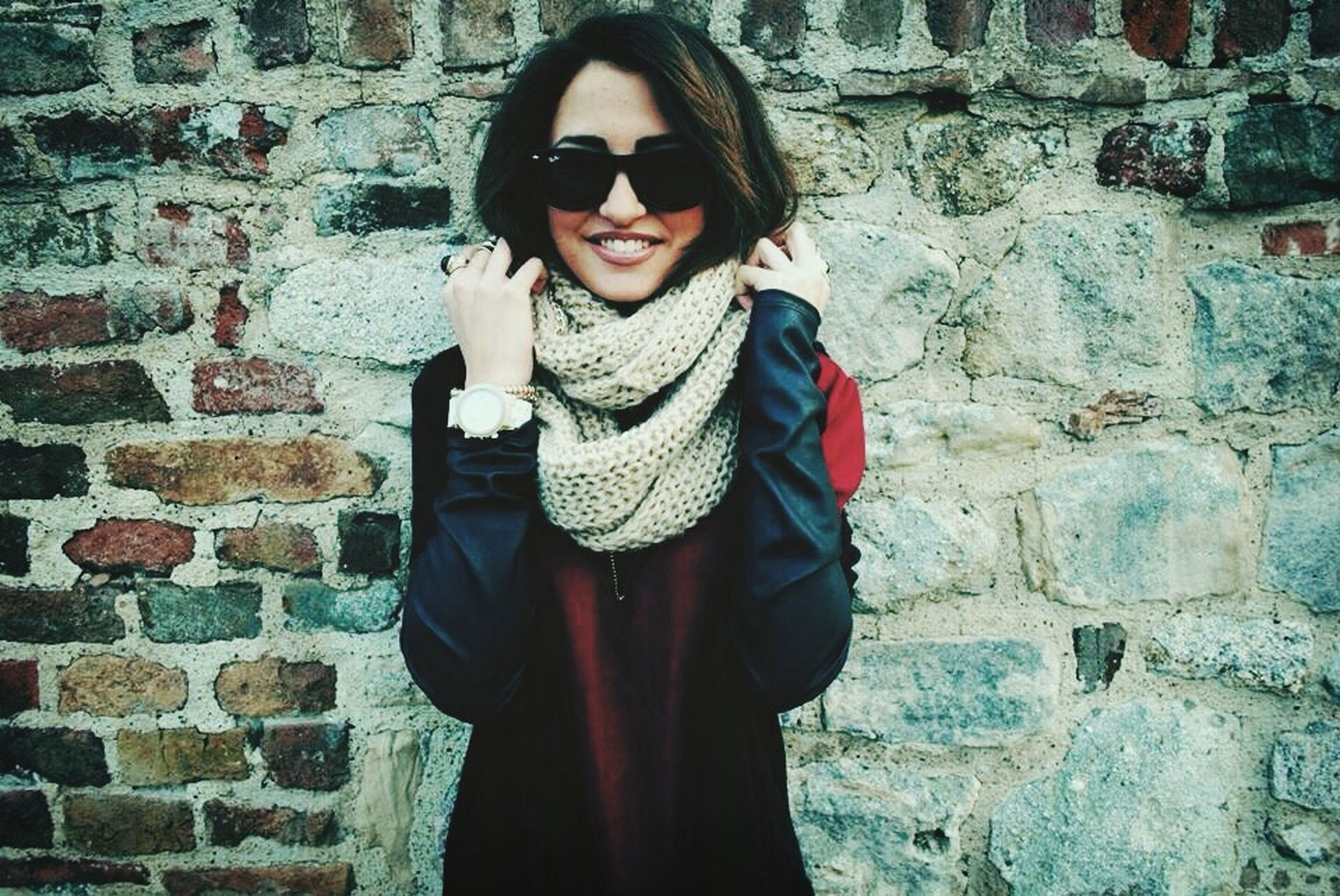 young adult, lifestyles, standing, young women, front view, portrait, casual clothing, person, looking at camera, leisure activity, wall - building feature, brick wall, three quarter length, sunglasses, smiling, built structure, fashion
