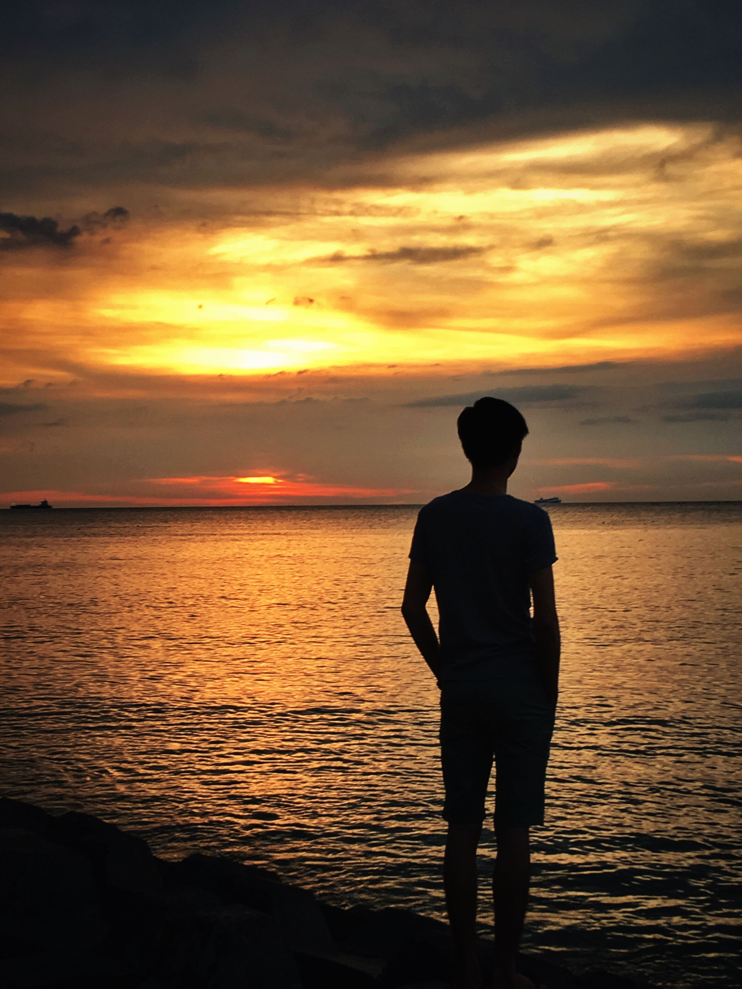 sunset, sea, horizon over water, sky, water, scenics, standing, lifestyles, beauty in nature, silhouette, leisure activity, tranquil scene, orange color, tranquility, cloud - sky, rear view, beach, idyllic