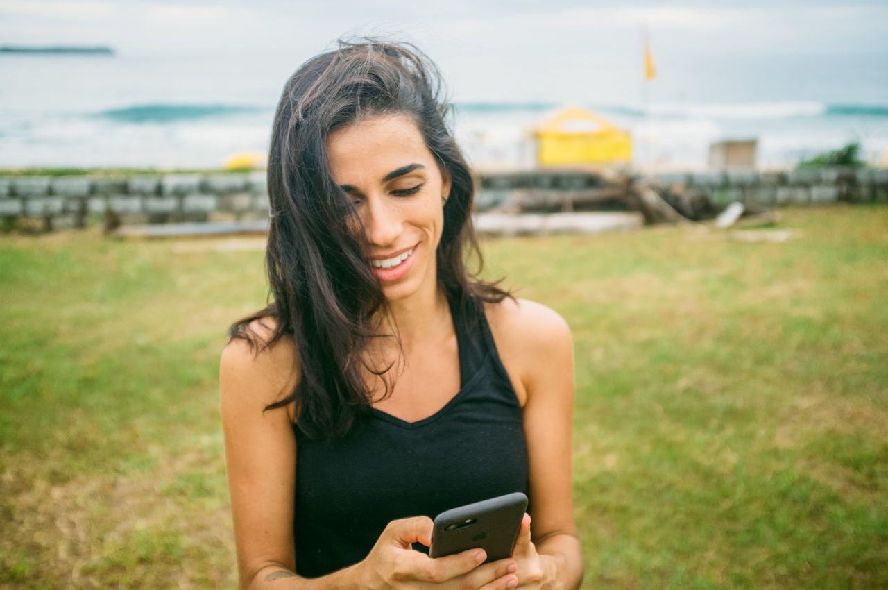 Beach Brazil Communication Day Florianópolis Focus On Foreground Grass Leisure Activity Lifestyles Mobile Phone One Person Outdoors Portable Information Device Real People Sky Smart Phone Smiling Technology Wireless Technology Young Adult Young Woman Young Women