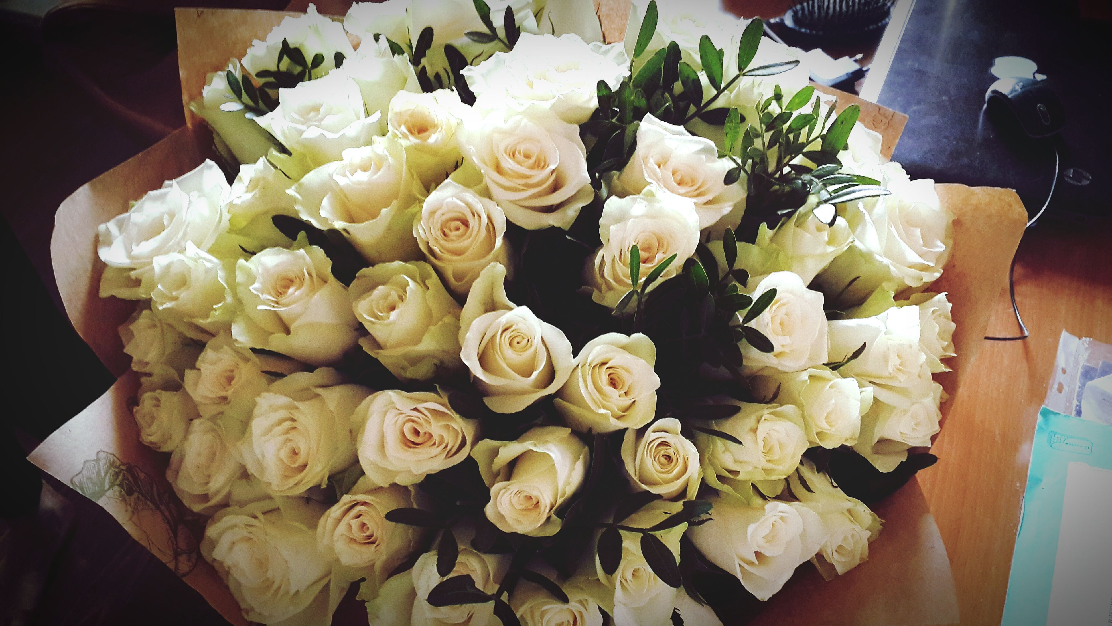 flower, freshness, indoors, petal, bouquet, vase, fragility, rose - flower, flower head, bunch of flowers, flower arrangement, high angle view, table, close-up, decoration, beauty in nature, rose, still life, white color, variation