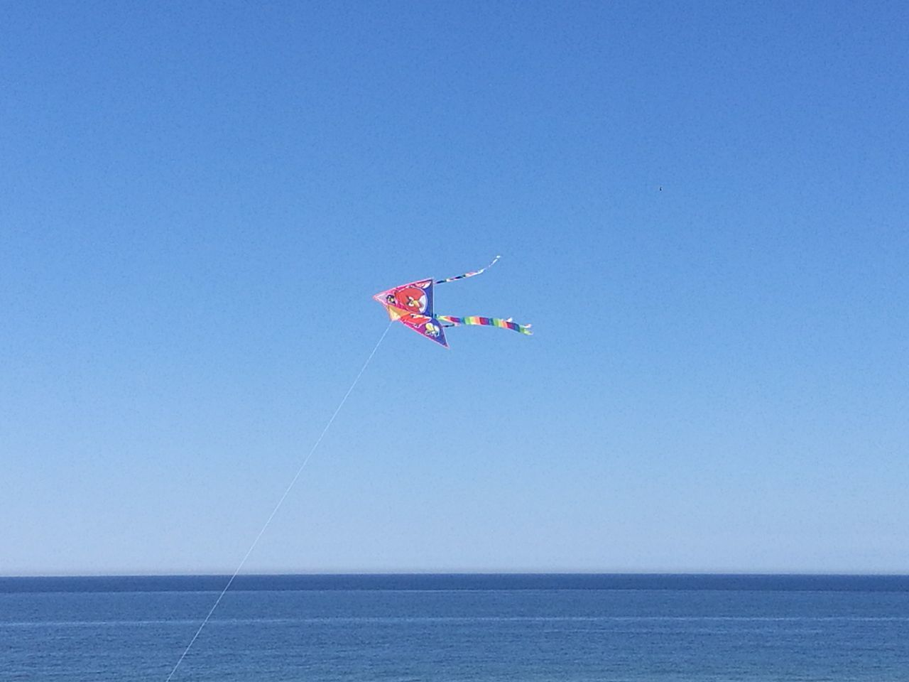 sea, clear sky, copy space, horizon over water, nature, kite, blue, water, day, outdoors, flying, beauty in nature, no people, scenics, sky