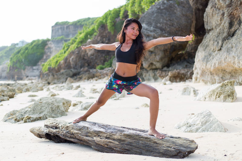 Young adult girl doing yoga. Adult Adults Only Bali Challenge Day Extreme Sports Full Length INDONESIA Nature One Person One Woman Only Only Women Outdoors People Real People Rock - Object Rock Climbing Skill  Strength Vitality Yoga Yoga Pose Morning Rituals Y Young Adult Neighborhood Map