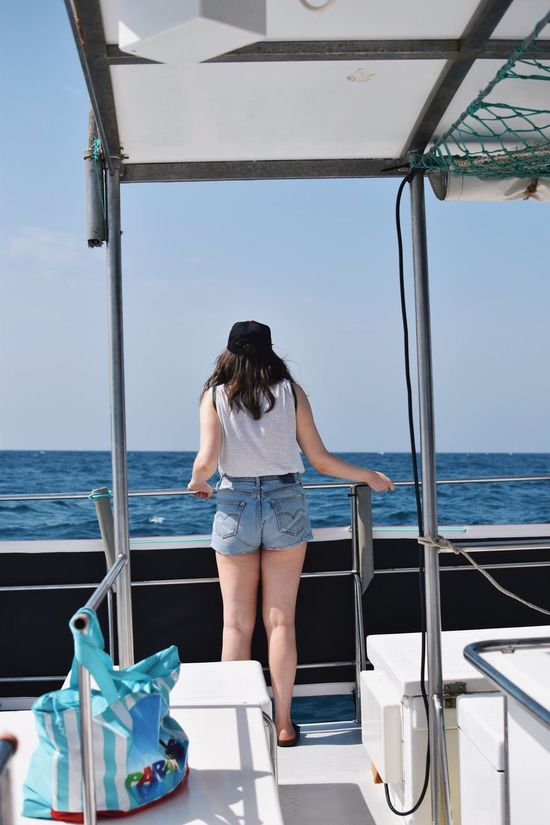 Beauty In Nature Boat Deck Casual Clothing Day Horizon Over Water Hot Pants Leisure Activity Lifestyles Nature Nautical Vessel One Person Outdoors People Real People Rear View Sailing Sea Sky Standing Summer Transportation Water Yacht Young Adult Young Women