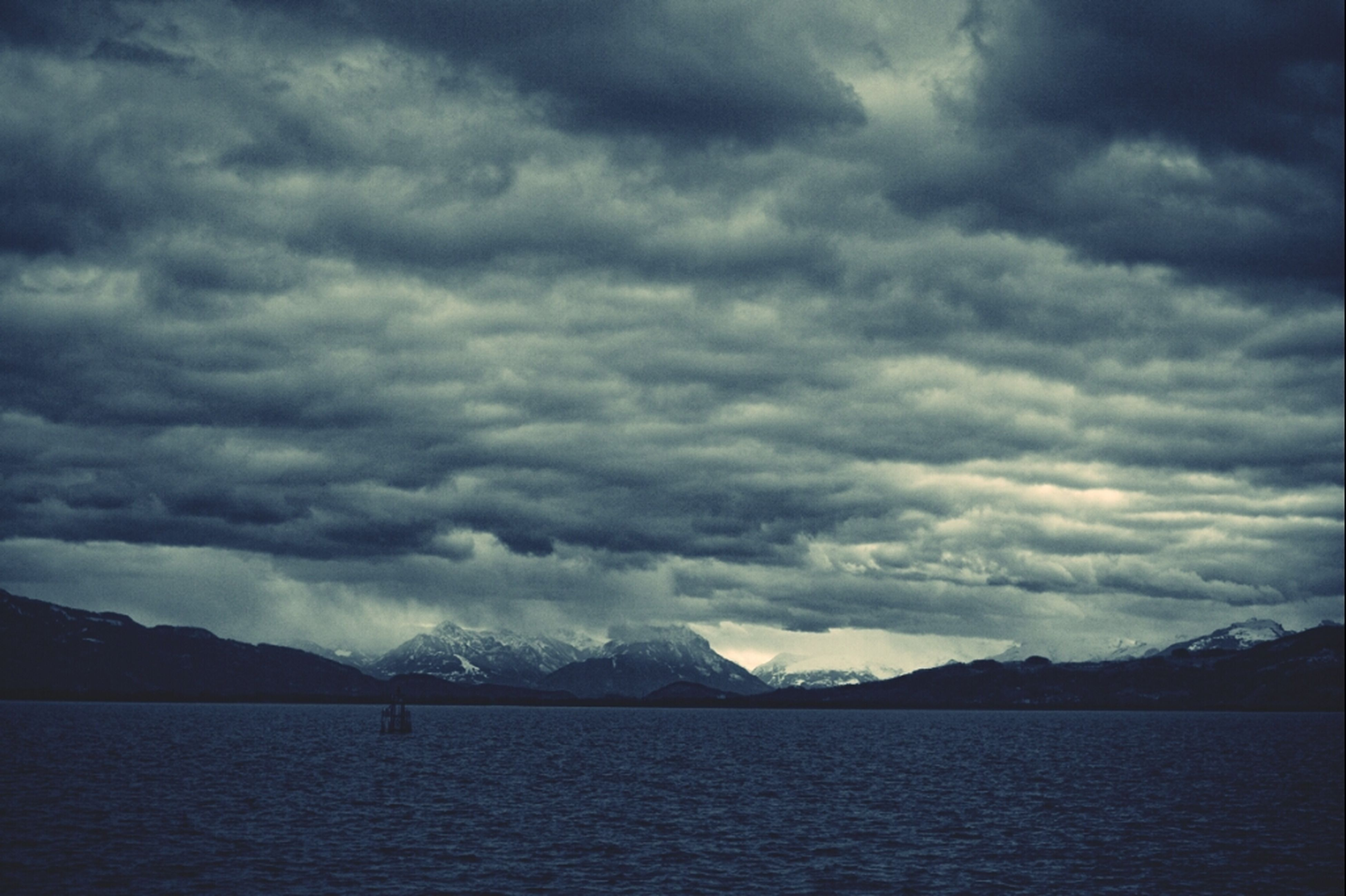 mountain, sky, tranquil scene, scenics, water, mountain range, tranquility, cloud - sky, beauty in nature, cloudy, waterfront, lake, nature, weather, cloud, idyllic, overcast, river, non-urban scene, outdoors