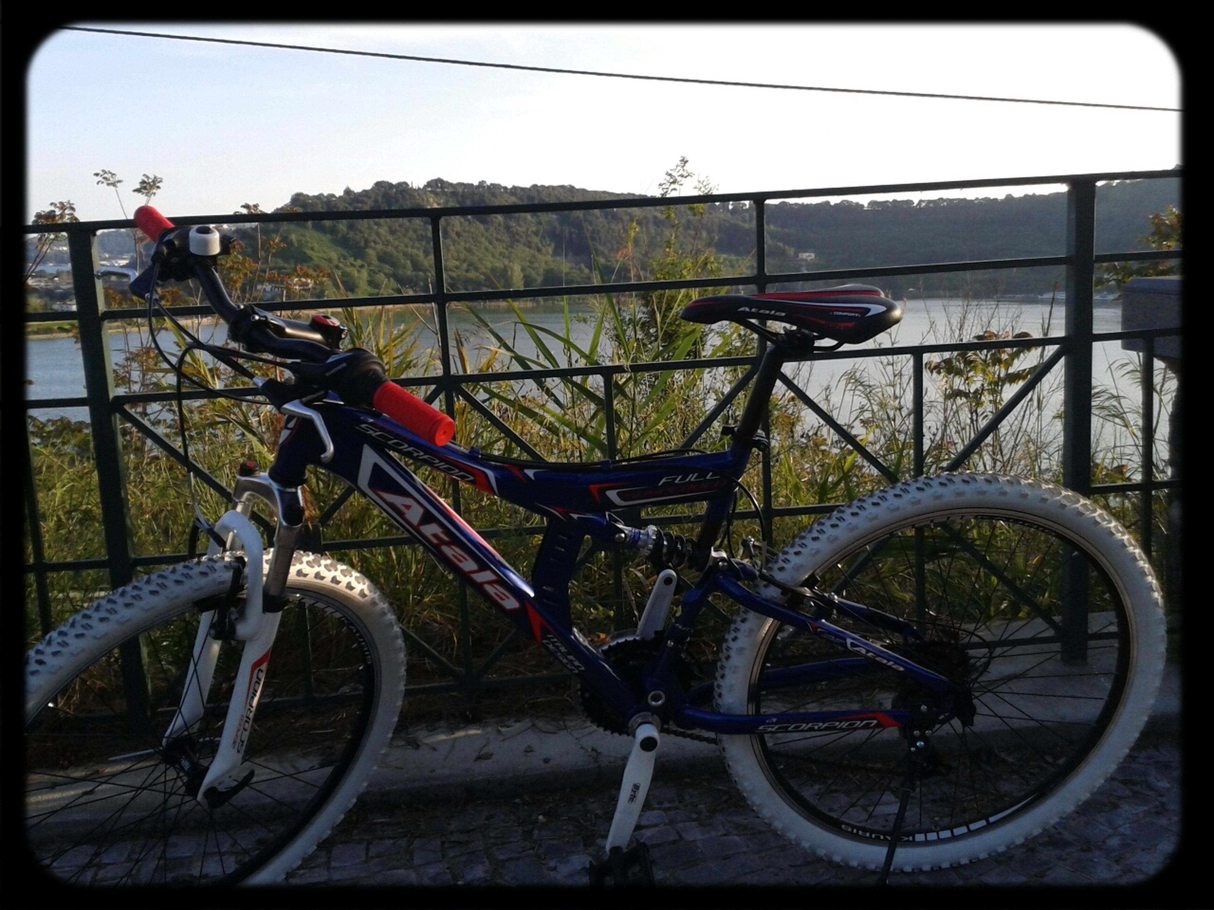 bicycle, transportation, mode of transport, land vehicle, transfer print, stationary, parked, auto post production filter, parking, car, travel, day, railing, outdoors, street, wheel, fence, riding, sky, cycle