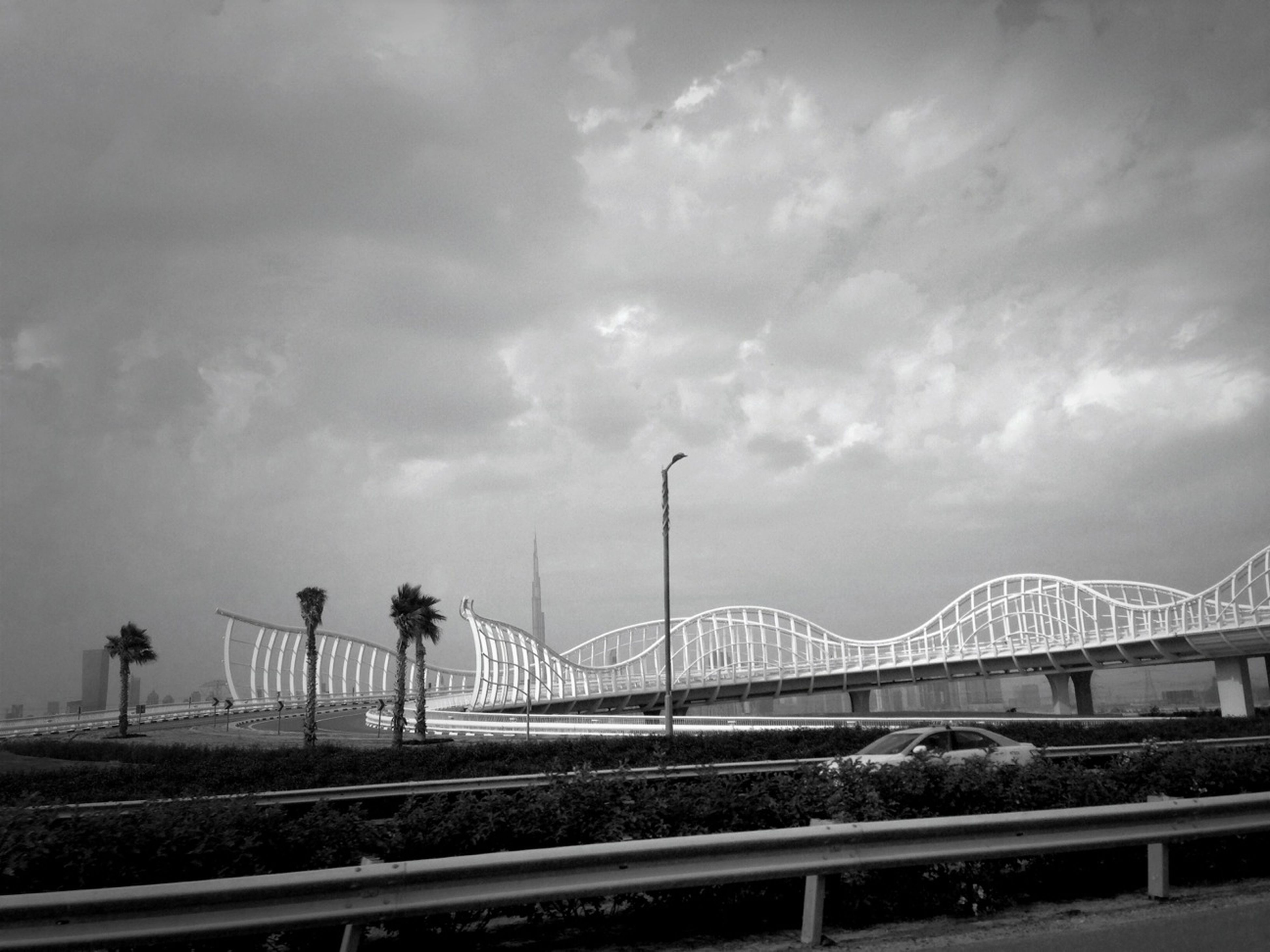 sky, cloud - sky, railing, built structure, architecture, connection, transportation, bridge - man made structure, cloudy, street light, cloud, road, building exterior, bridge, engineering, city, the way forward, overcast, outdoors, day