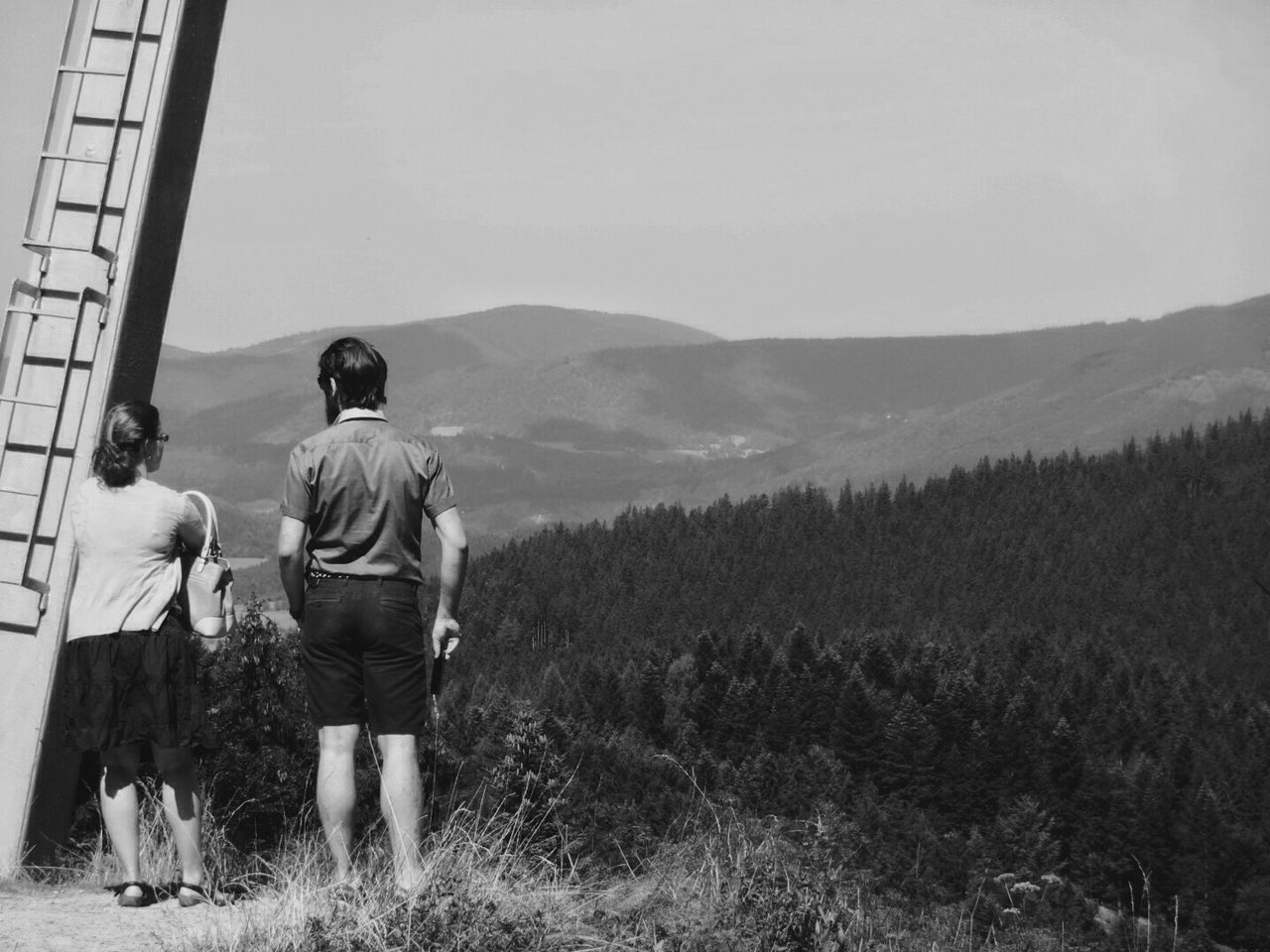 togetherness, rear view, mountain, nature, real people, full length, men, casual clothing, pets, two people, leisure activity, friendship, day, standing, dog, sky, outdoors, lifestyles, beauty in nature, bonding, grass, mammal, adult, people