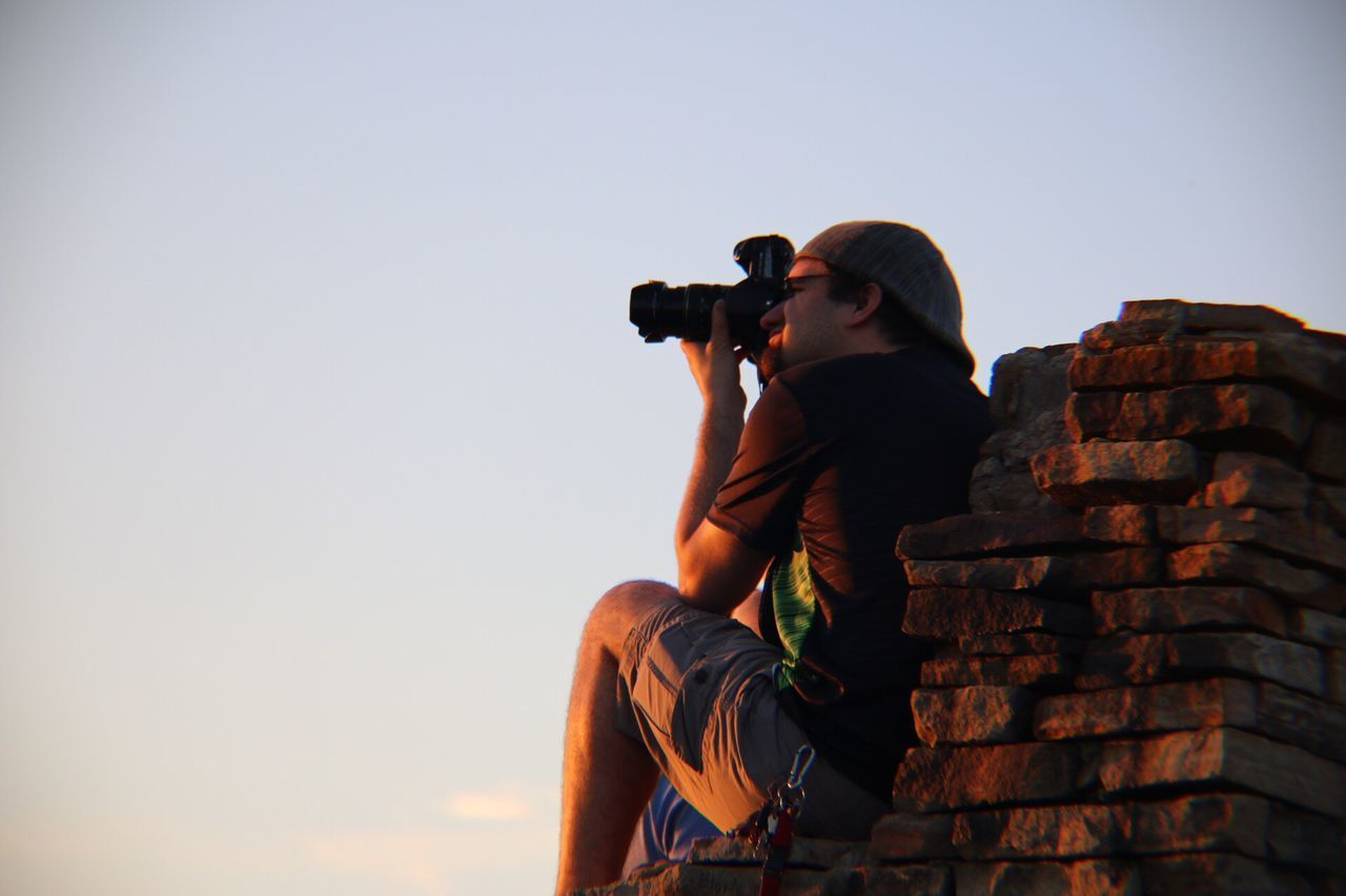 Camera - Photographic Equipment Photographing Photography Themes Leisure Activity Clear Sky Real People Photographer Standing Sky Day Outdoors Low Angle View Technology Men One Person Nature Digital Single-lens Reflex Camera Young Adult People