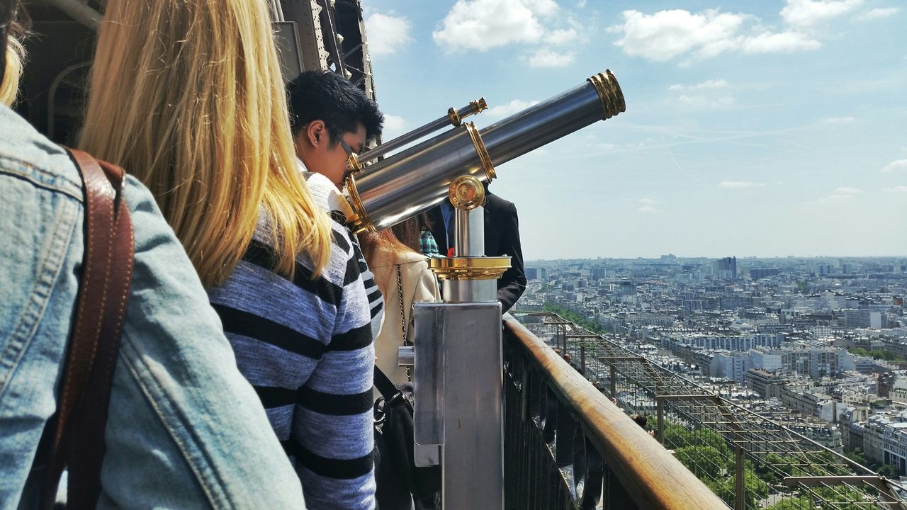 real people, outdoors, building exterior, built structure, architecture, day, city, cityscape, coin-operated binoculars, leisure activity, hand-held telescope, young adult, one person, young women, sky, lifestyles