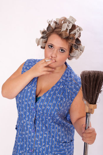 Smoking young charwoman with big bust and curlers in her hair, in a hand holding a broom. Apron Curlers  Hair Housekeeper Housewife Smoke Work Boobs, Break Brush Chubby Cigarette  Cleaning Service Cleavage Curvy Domestic Help Fat Holding Job Overweight Plus Plussize Rest Size Women