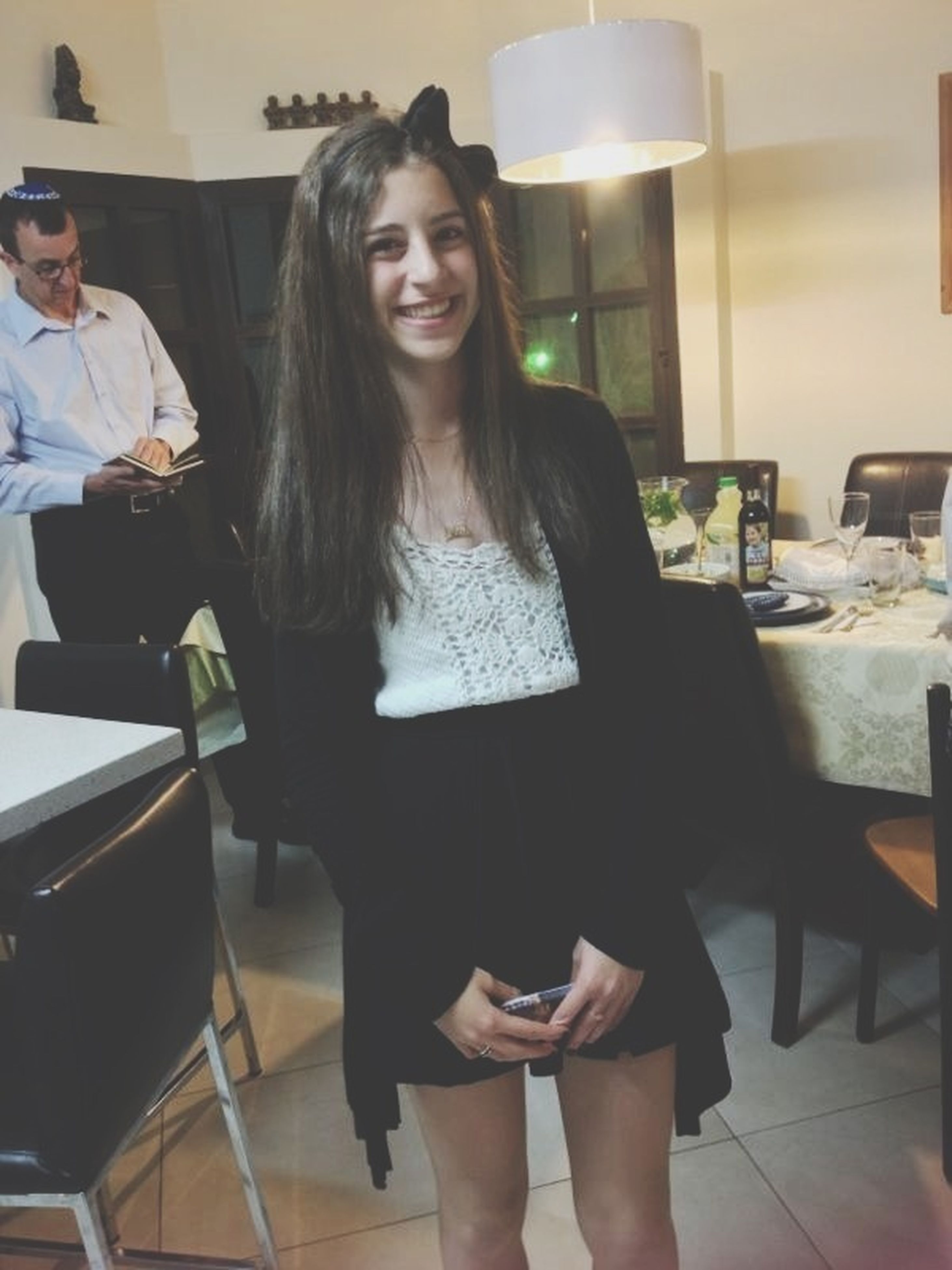 indoors, young adult, young women, lifestyles, sitting, leisure activity, casual clothing, person, long hair, front view, standing, home interior, chair, table, three quarter length, looking at camera
