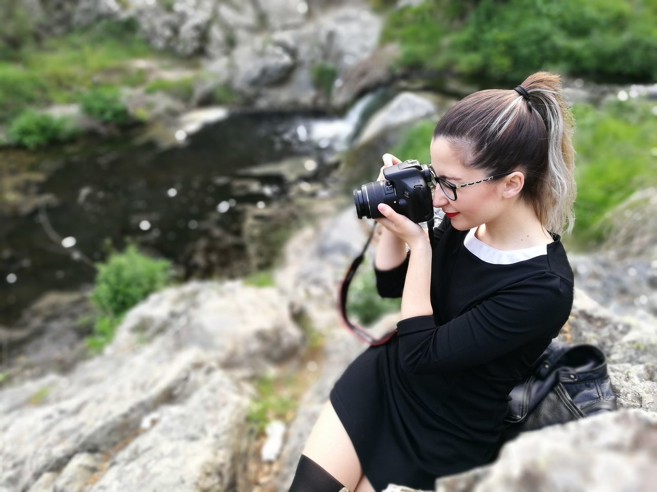 camera - photographic equipment, real people, photography themes, leisure activity, young women, digital single-lens reflex camera, one person, photographing, young adult, water, outdoors, rock - object, photographer, lifestyles, digital camera, day, casual clothing, technology, sitting, nature, women, slr camera, waterfall
