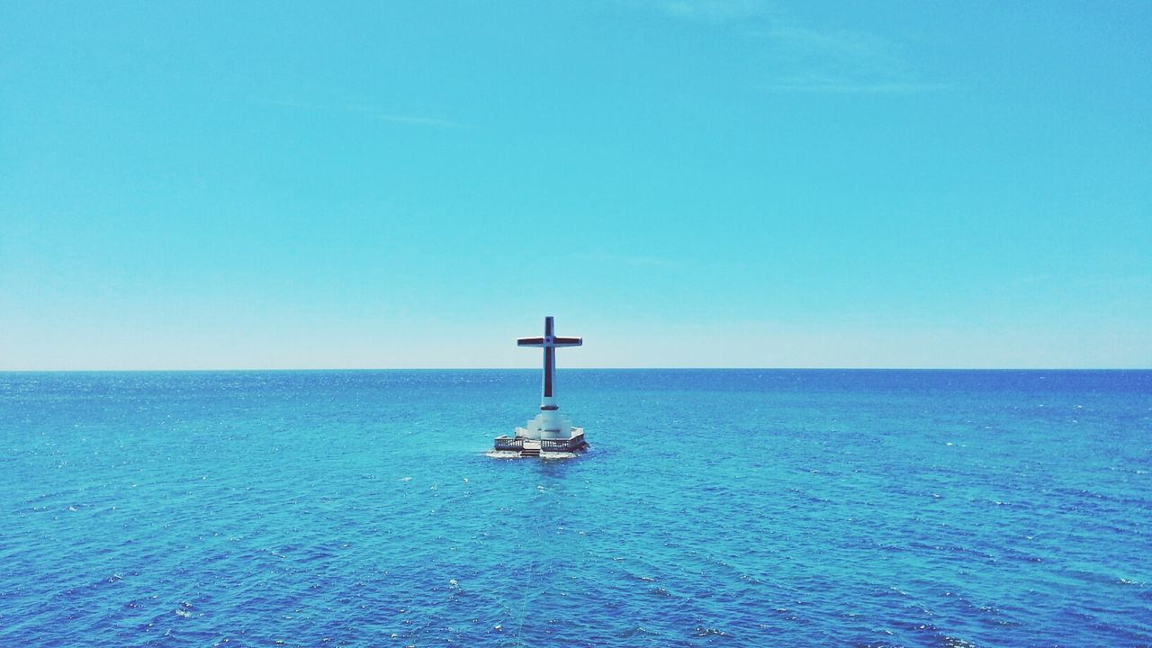 Cross Sculpture Amidst Blue Sea Against Clear Sky