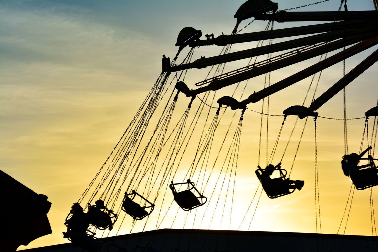 Low Angle View Of Silhouette People Enjoying Swing Ride Against Sky During Sunset
