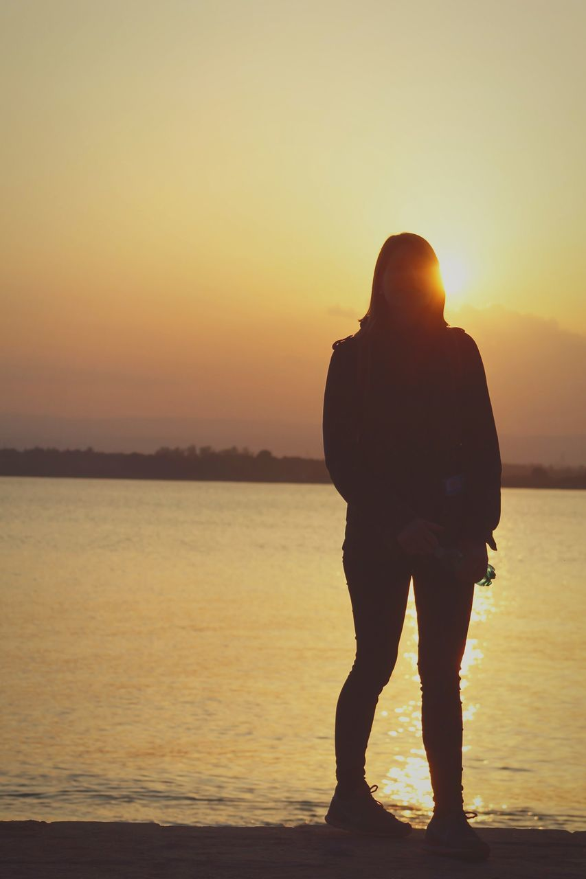 Full Length Rear View Of Woman Standing Against River And Sky During Sunset