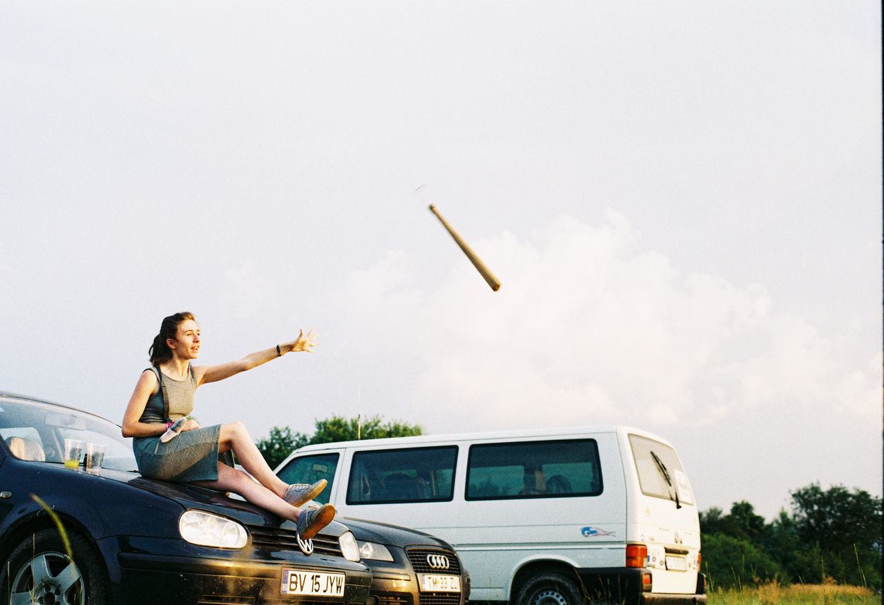 Baseball Baseball Bat Car Cars Movement Sitting Sitting Outside Throwing  Transportation Young Adult