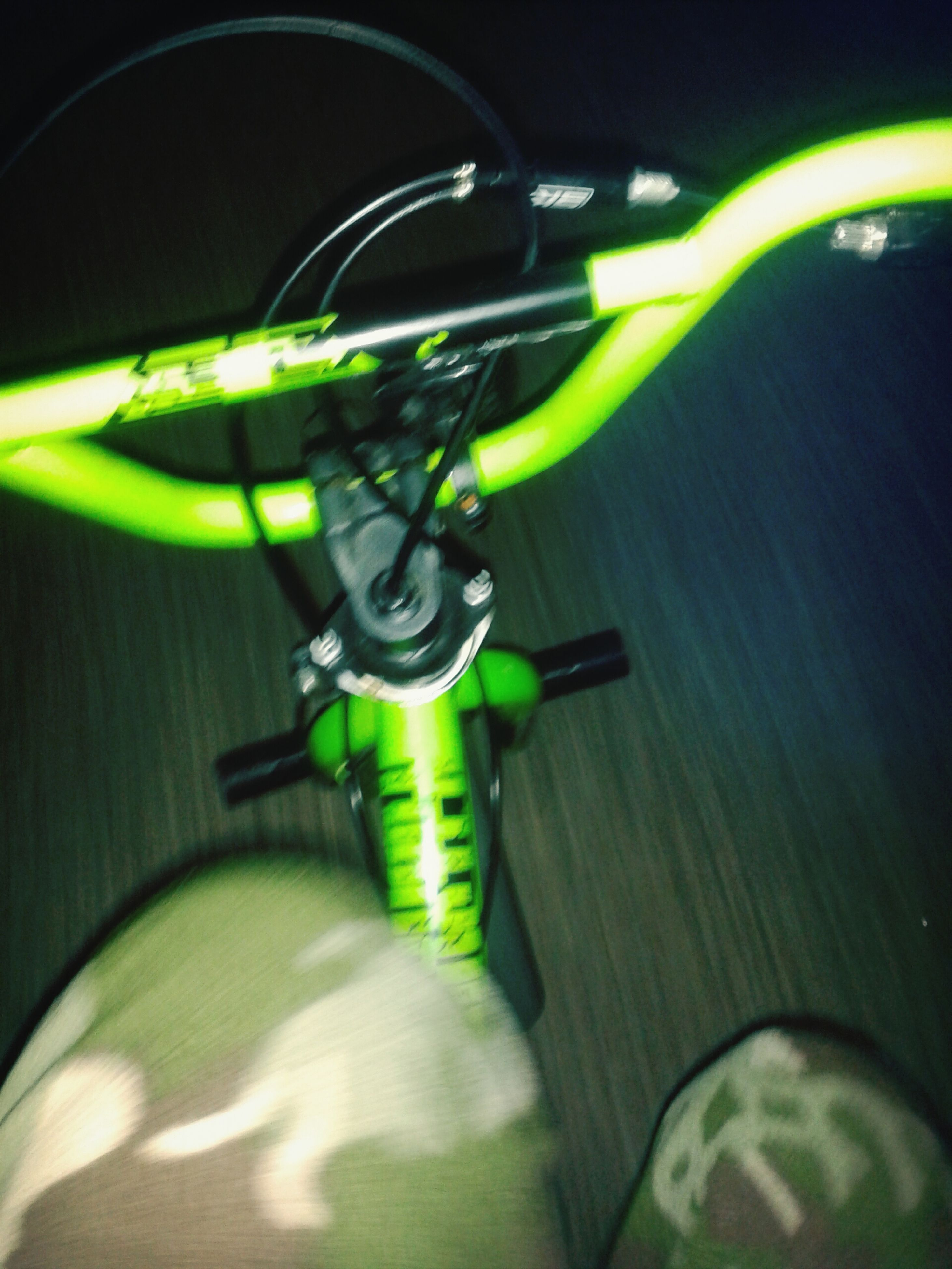 green color, indoors, night, bicycle, high angle view, sport, childhood, transportation, close-up, illuminated, circle, selective focus, shadow, land vehicle, toy, sunlight, still life