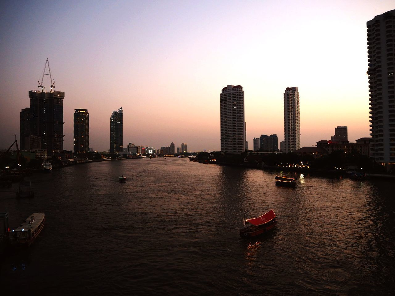 skyscraper, building exterior, architecture, sunset, city, built structure, cityscape, waterfront, urban skyline, river, outdoors, water, travel destinations, modern, clear sky, sky, no people, tall, nature, day
