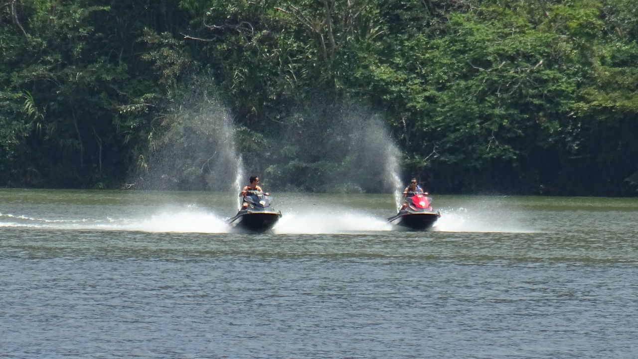 Adventure Beauty In Nature Day Jet Boat Large Group Of People Leisure Activity Lifestyles Men Motion Nature Nautical Vessel Oar Outdoors People Rafting Real People River Rowing Spraying Transportation Tree Vacations Water Waterfront Women