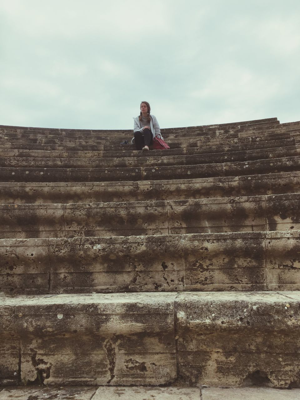 Low Angle View Of Woman Sitting At Amphitheater Against Sky