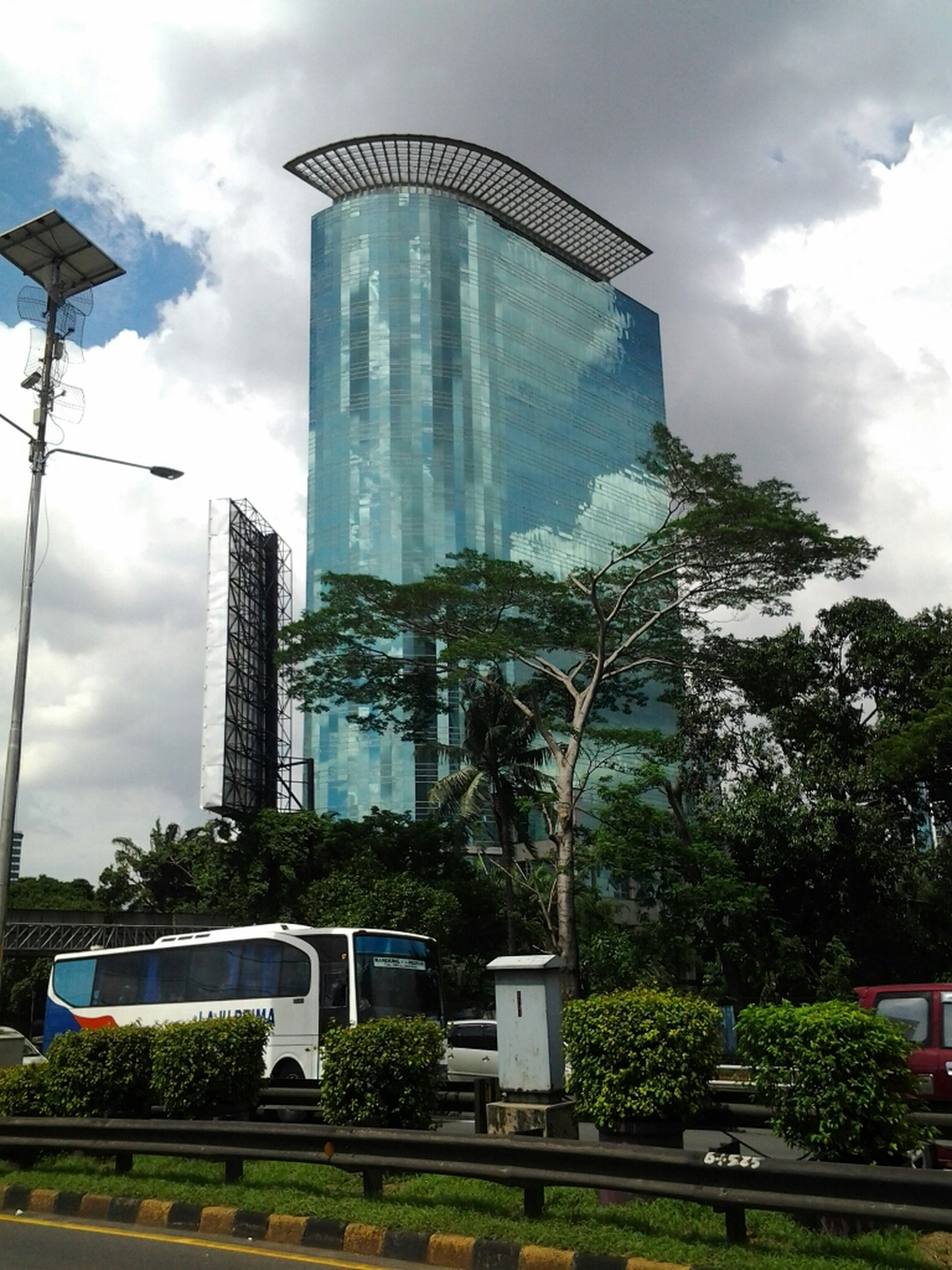 building exterior, architecture, built structure, sky, tree, cloud - sky, city, cloud, modern, office building, building, cloudy, growth, low angle view, skyscraper, day, tall - high, tower, glass - material, city life