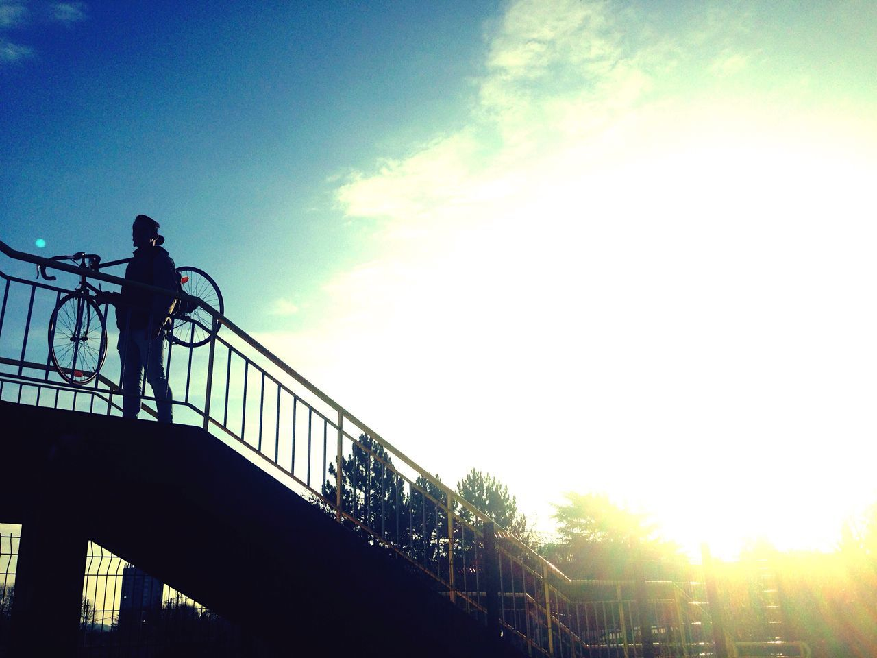 Low Angle View Of Silhouette Person Walking On Bridge