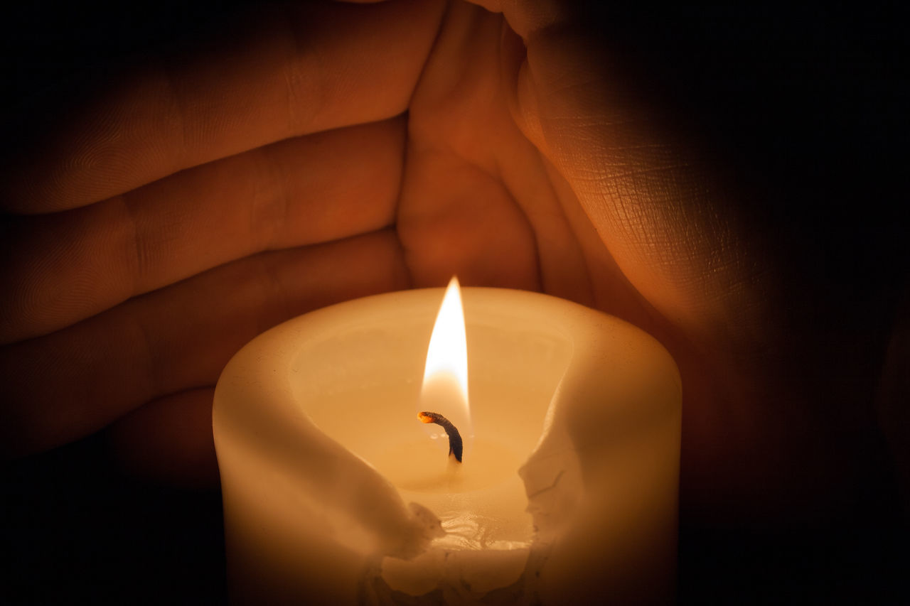 Cropped Hand Of Person By Burning Candle
