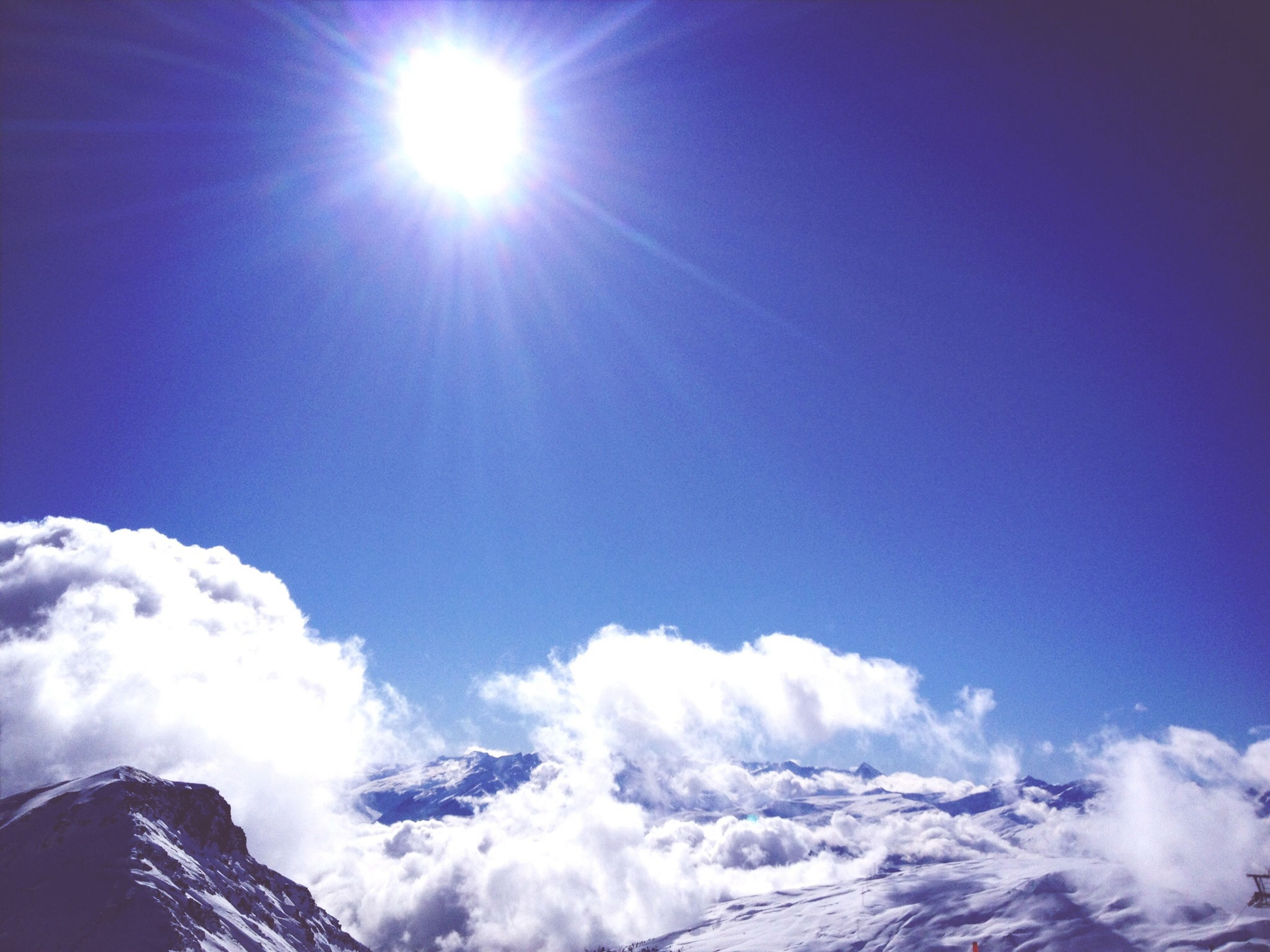 sun, sunbeam, tranquility, sunlight, beauty in nature, low angle view, scenics, tranquil scene, sky, blue, snow, mountain, nature, lens flare, cold temperature, winter, sunny, bright, idyllic, day