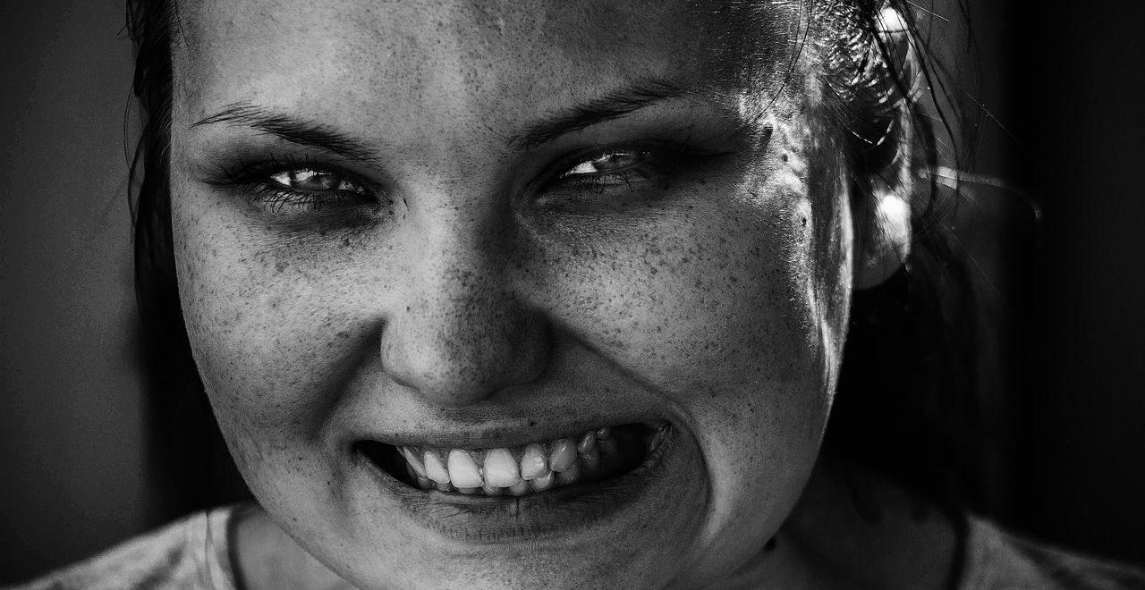 Close-Up Portrait Of Woman Clenching Teeth